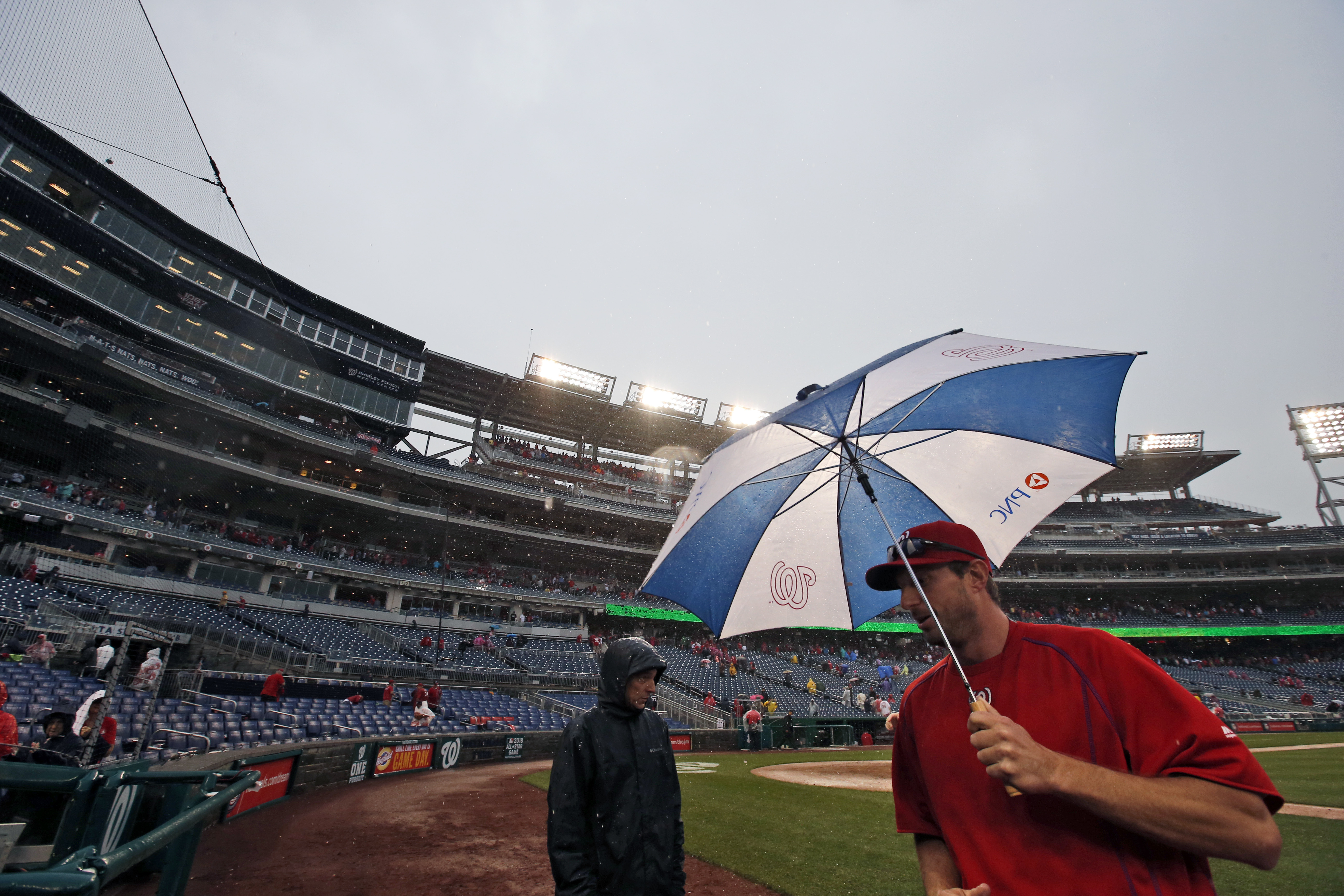 Washington Nationals starting pitcher Max Scherzer uses an umbrella to go the field in the rain after the first baseball game of a split doubleheader against the Miami Marlins at Nationals Park, Saturday, May 14, 2016, in Washington. (AP Photo/Alex Brando
