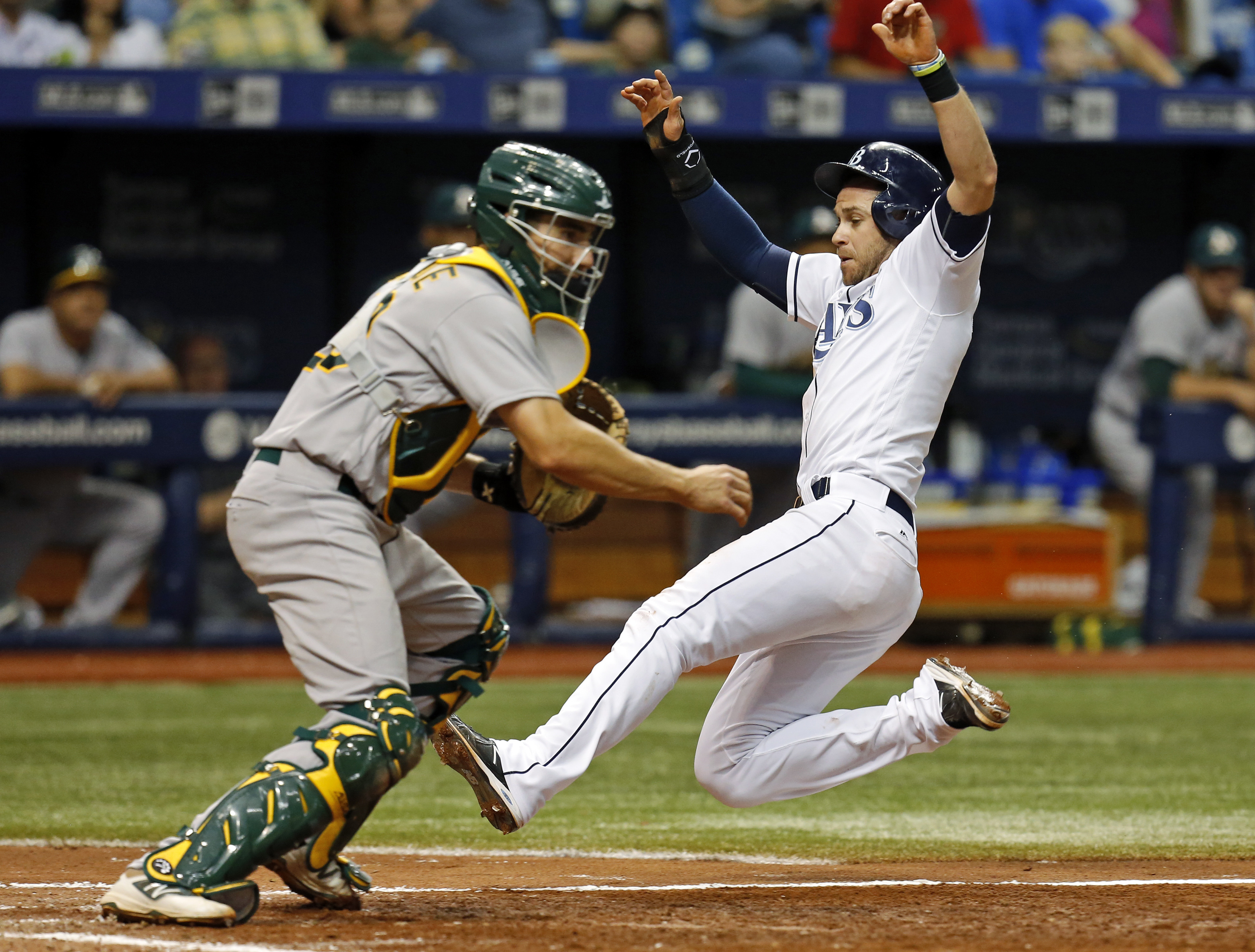 Tampa Bay Rays' Evan Longoria slides in behind Oakland Athletics catcher Matt McBride to score on a sacrifice fly during the sixth inning of a baseball game Saturday, May 14, 2016, in St. Petersburg, Fla. (AP Photo/Mike Carlson)
