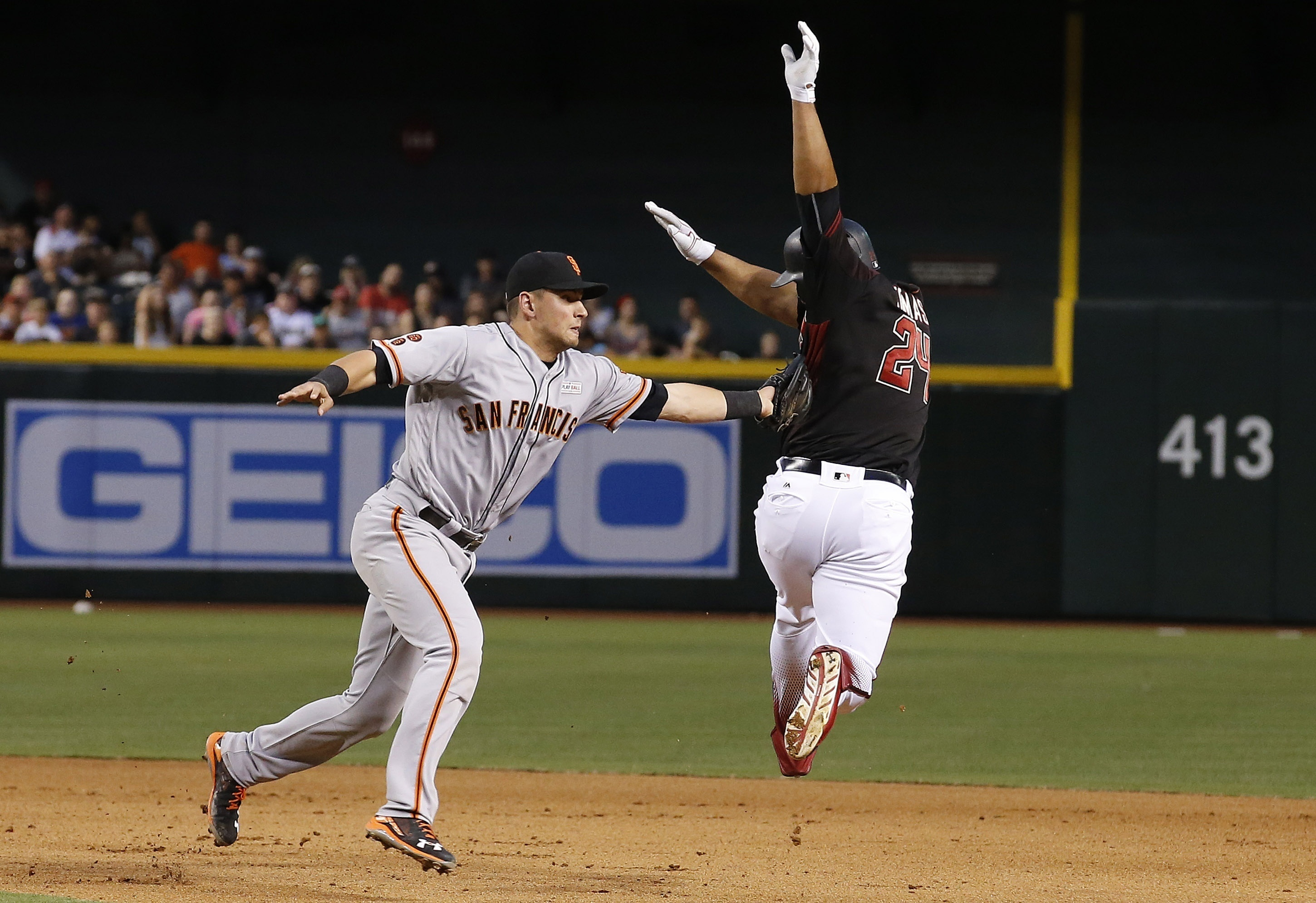 San Francisco Giants' Joe Panik, left, tags out Arizona Diamondbacks' Yasmany Tomas, right, as Tomas tries to get to second base during the seventh inning of a baseball game Saturday, May 14, 2016, in Phoenix. (AP Photo/Ross D. Franklin)