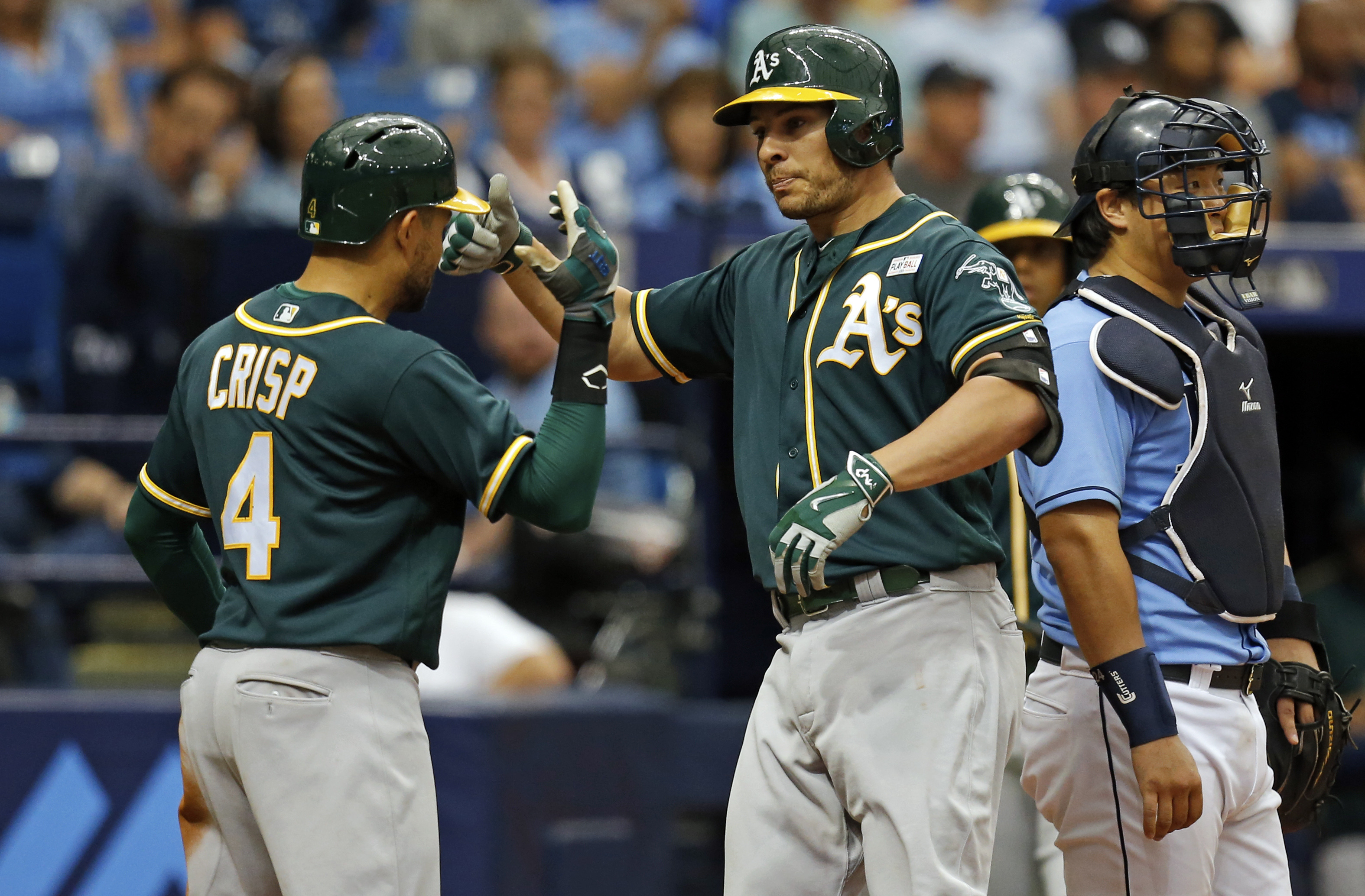 Oakland Athletics' Danny Valencia, center, is congratulated by Coco Crisp (4) in front of Tampa Bay Rays catcher Hank Conger after his home run scored them both during the fifth inning of a baseball game Sunday, May 15, 2016, in St. Petersburg, Fla. (AP P