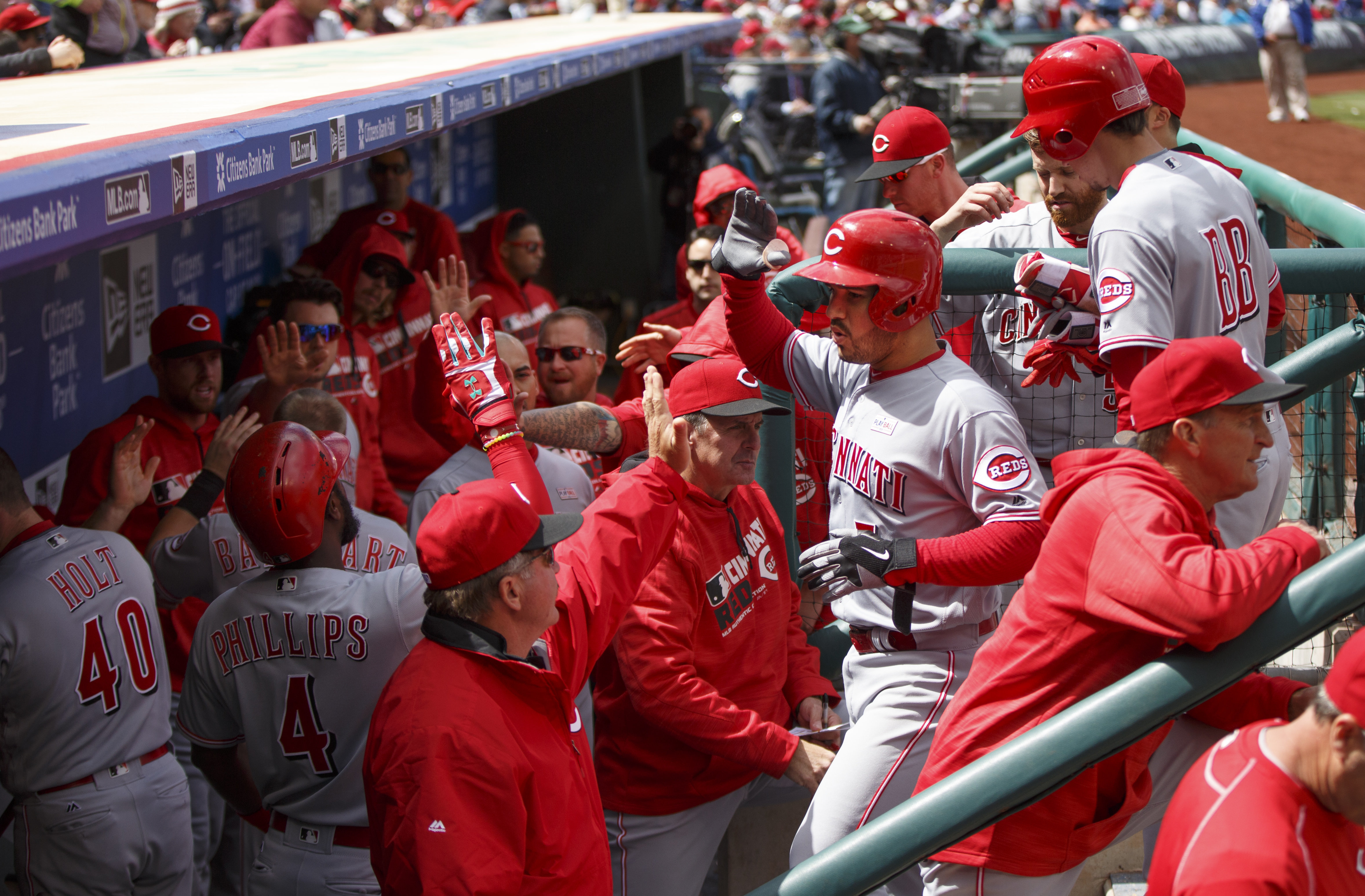 Cincinnati Reds' Eugenio Suarez, center right, celebrates his three-run home run with teammates in the dugout during the fourth inning of a baseball game against the Philadelphia Phillies, Sunday, May 15, 2016, in Philadelphia. (AP Photo/Chris Szagola)