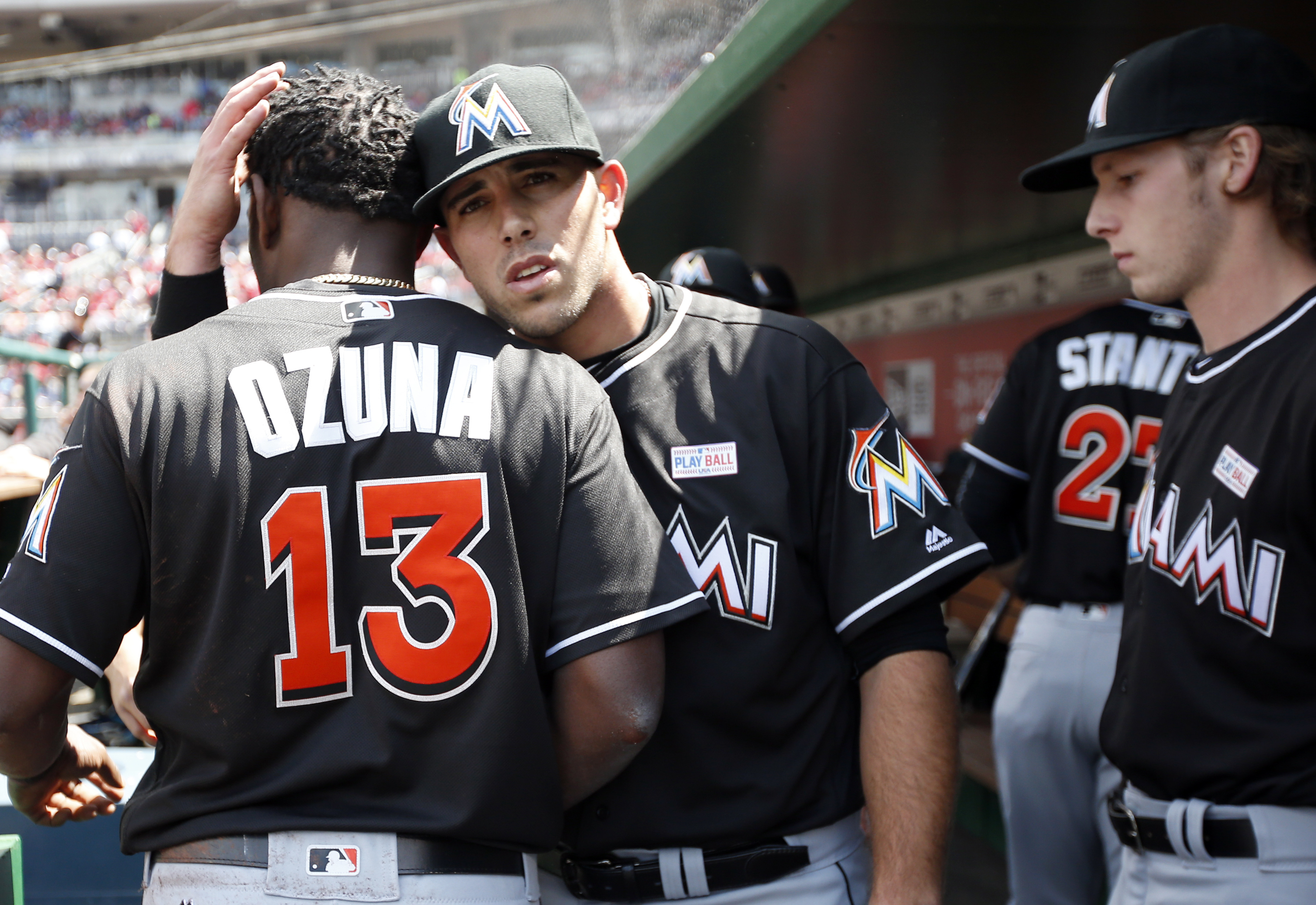 Miami Marlins starting pitcher Jose Fernandez, center, hugs center fielder Marcell Ozuna after his collision with Giancarlo Stanton as Adam Conley, right, stands by during the fourth inning of a baseball game against the Washington Nationals at Nationals