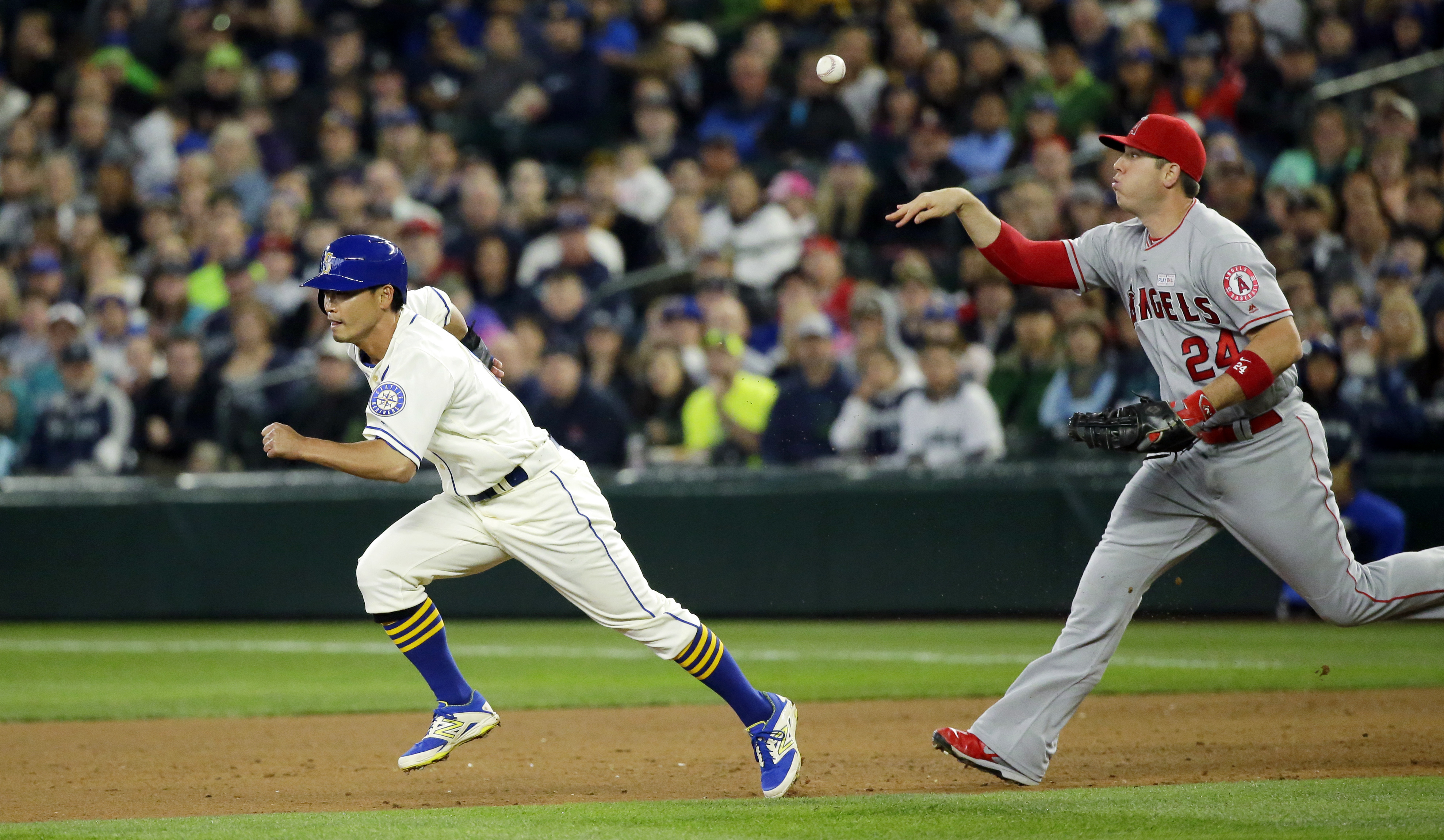 Los Angeles Angels' C.J. Cron, right, throws to Angels' Gregorio Peti to get Seattle Mariners' Norichika Aoki, left, out in a rundown as Aoki attempts to steal second base in the sixth inning of a baseball game, Sunday, May 15, 2016, in Seattle. (AP Photo