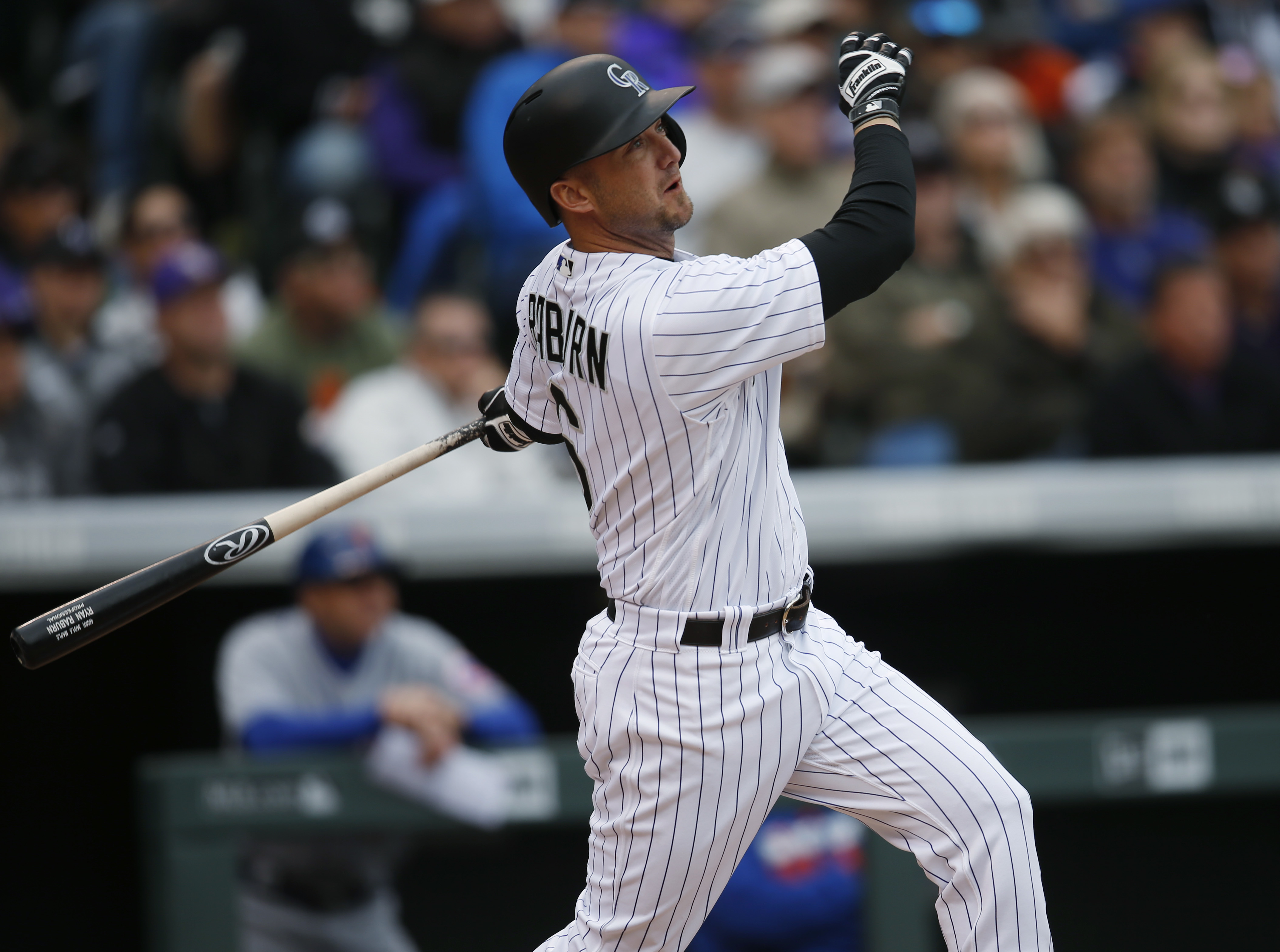 Colorado Rockies pinch hitter Ryan Raburn follows the flight of his two-run home run off New York Mets relief pitcher Jim Henderson in the seventh inning of a baseball game Sunday, May 15, 2016, in Denver. (AP Photo/David Zalubowski)