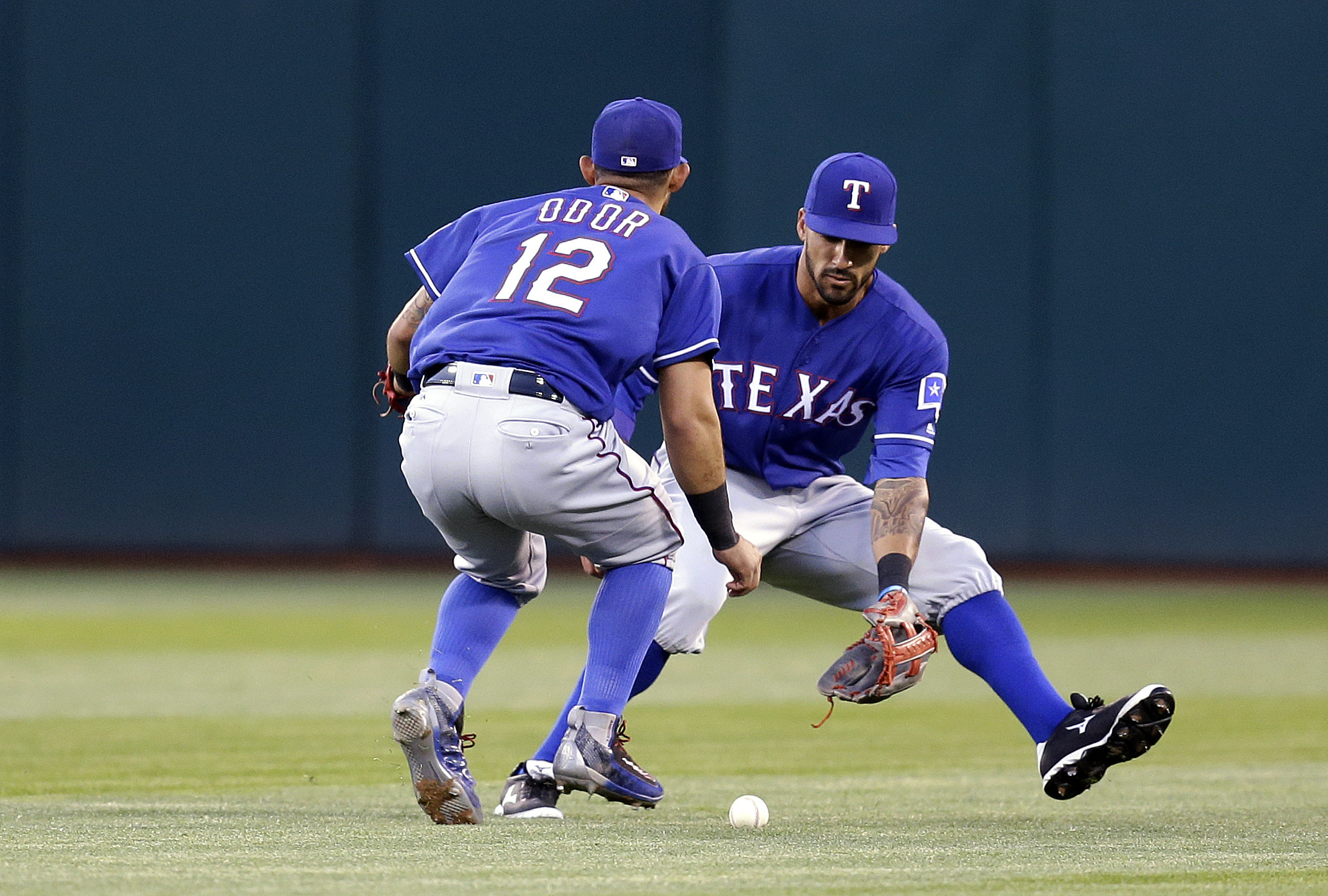 Texas Rangers' Rougned Odor (12) and Ian Desmond, right, field a ball hit for a single by Oakland Athletics' Josh Reddick in the fourth inning of a baseball game, Monday, May 16, 2016, in Oakland, Calif. (AP Photo/Ben Margot)