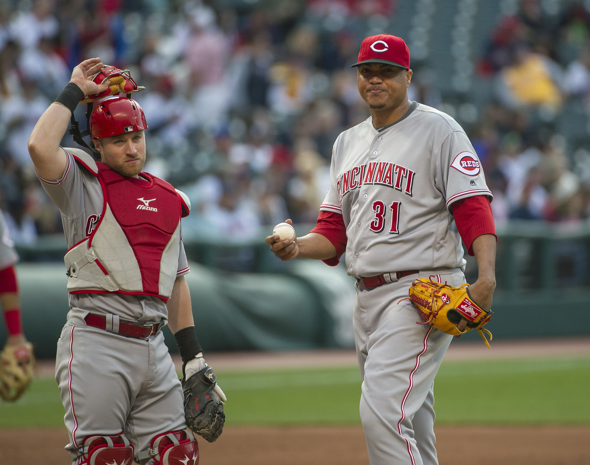 Cincinnati Reds starter Alfredo Simon prepares to leave the game as catcher Tucker Barnhart watches, during the fifth inning of a baseball game in Cleveland, Tuesday, May 17, 2016. (AP Photo/Phil Long)