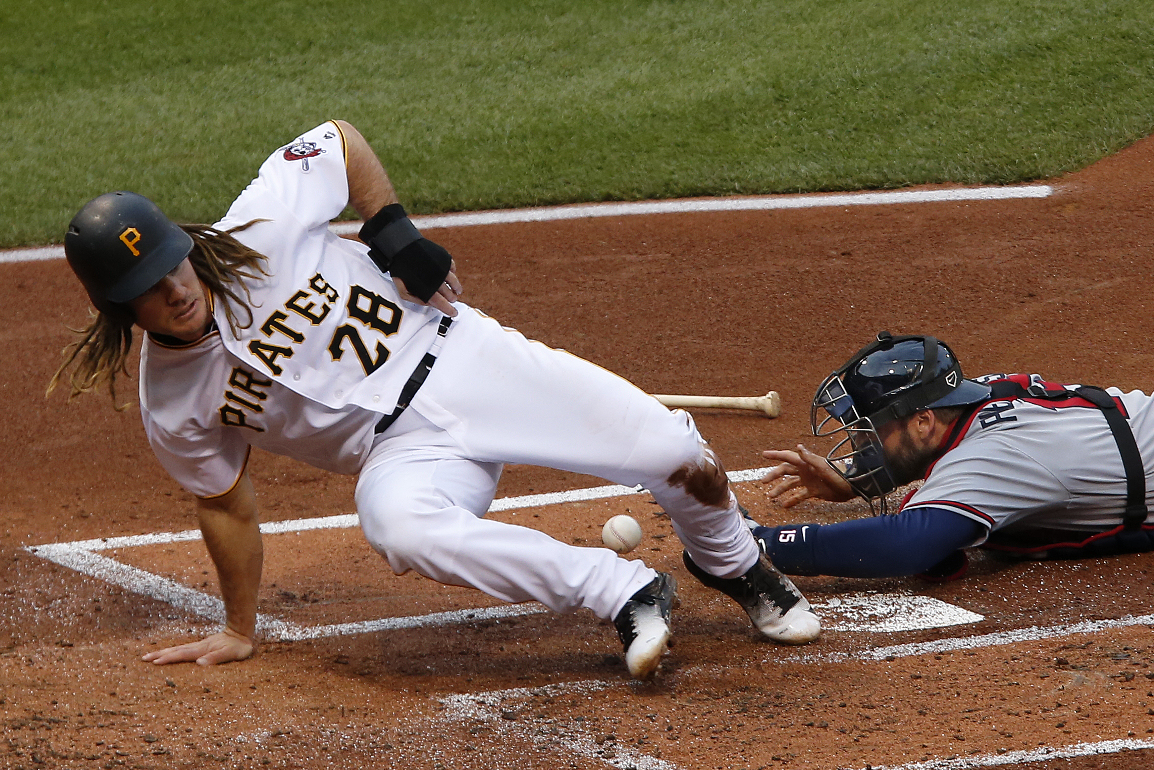 Pittsburgh Pirates' John Jaso (28) knocks the ball out of the glove of Atlanta Braves catcher A.J. Pierzynski to score on a ball hit by Jung Ho Kang during the first inning of a baseball game in Pittsburgh, Tuesday, May 17, 2016. (AP Photo/Gene J. Puskar)