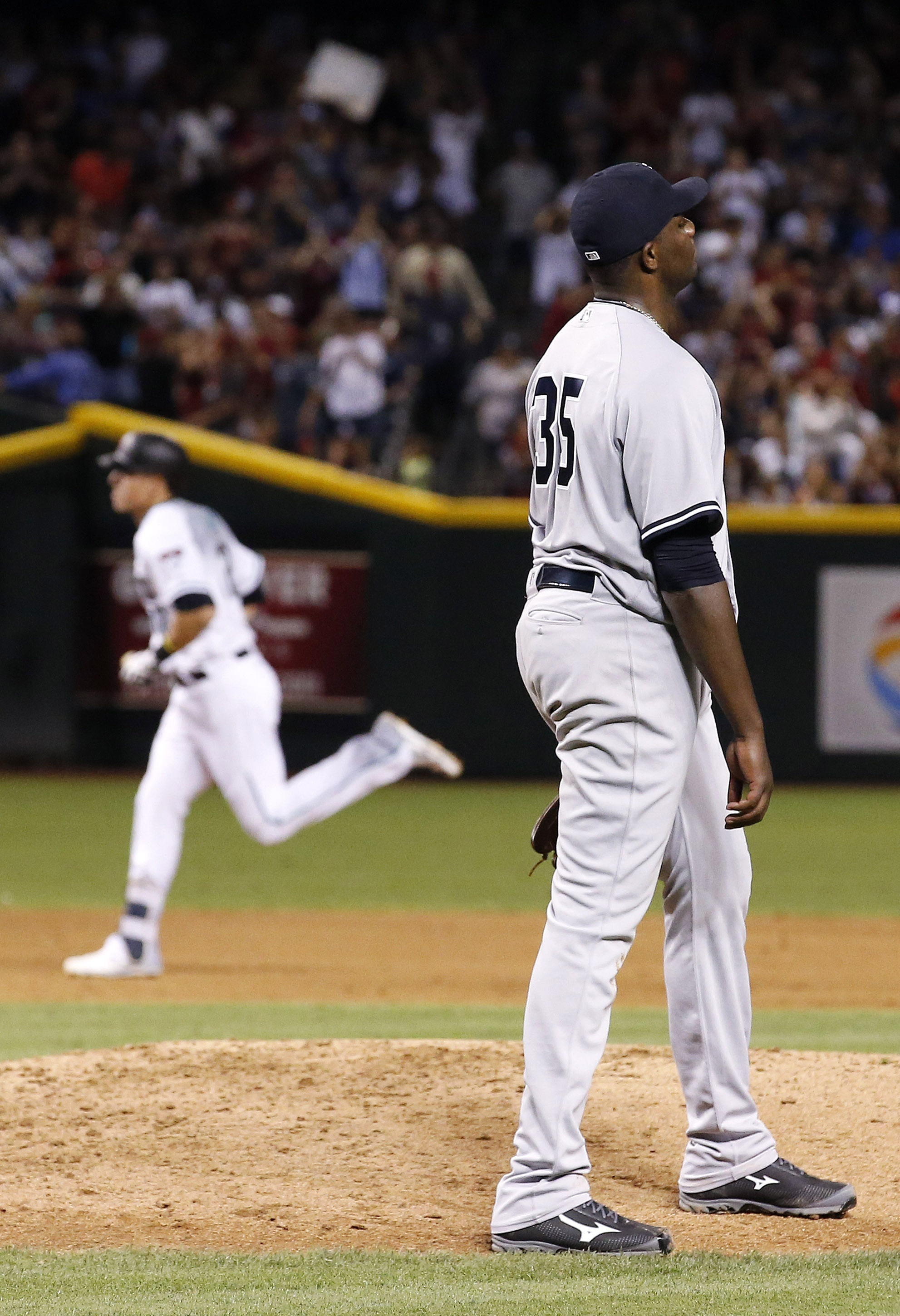 New York Yankees' Michael Pineda (35) pauses at the mound after giving up a two-run home run to Arizona Diamondbacks' Jake Lamb, rear, during the fifth inning of a baseball game Tuesday, May 17, 2016, in Phoenix. (AP Photo/Ross D. Franklin)