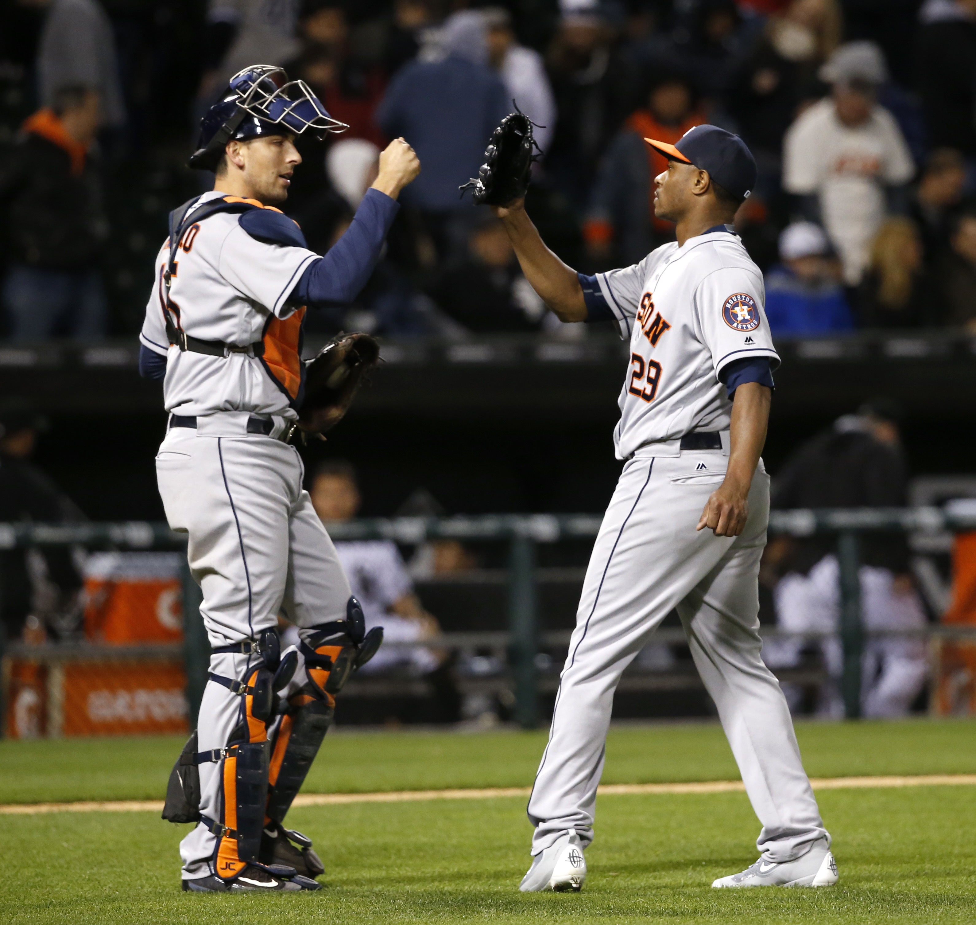 Houston Astros catcher Jason Castro, left, and relief pitcher Tony Sipp celebrate the Astros' 6-5 win over the Chicago White Sox in 11 innings in a baseball game Tuesday, May 17, 2016, in Chicago. (AP Photo/Charles Rex Arbogast)