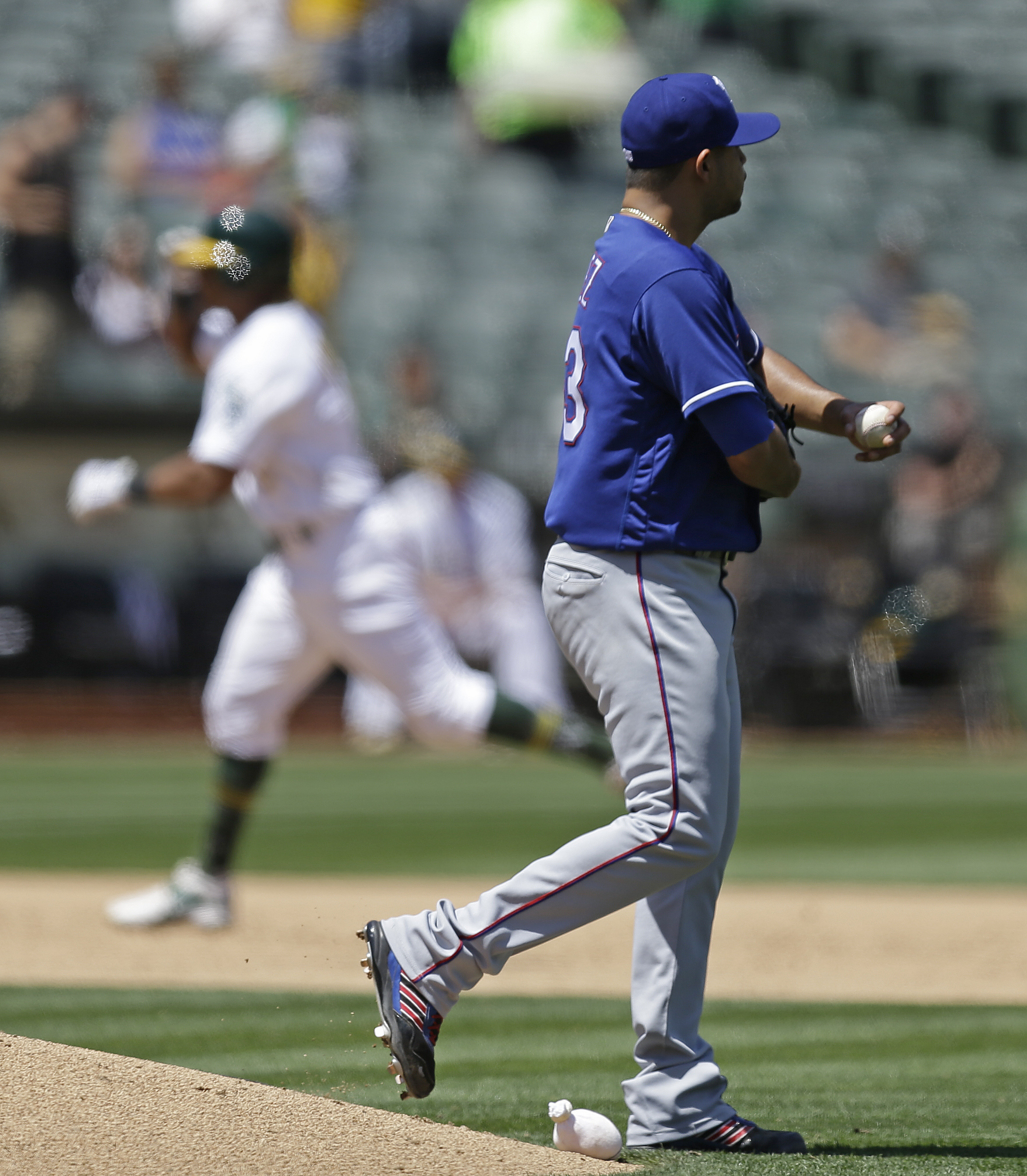 Texas Rangers pitcher Martin Perez, right, walks off the mound as he waits for Oakland Athletics' Khris Davis, left, to run the bases after hitting a home run in the sixth inning of a baseball game, Wednesday, May 18, 2016, in Oakland, Calif. (AP Photo/Be