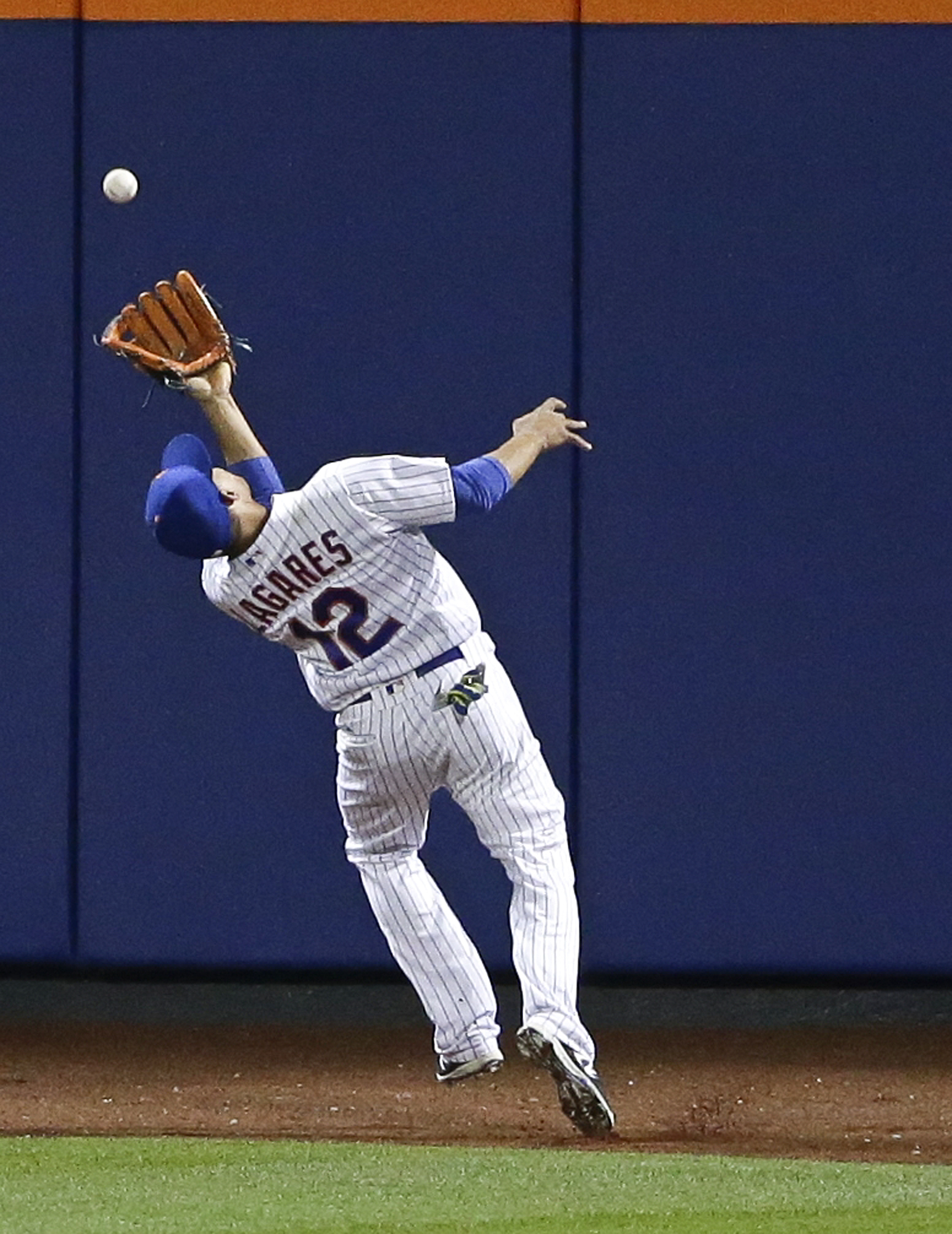 New York Mets center fielder Juan Lagares (12) catches a ball hit by Washington Nationals' Daniel Murphy for an out during the seventh inning of a baseball game Wednesday, May 18, 2016, in New York. Ben Revere tagged up to score on the play. (AP Photo/Fra