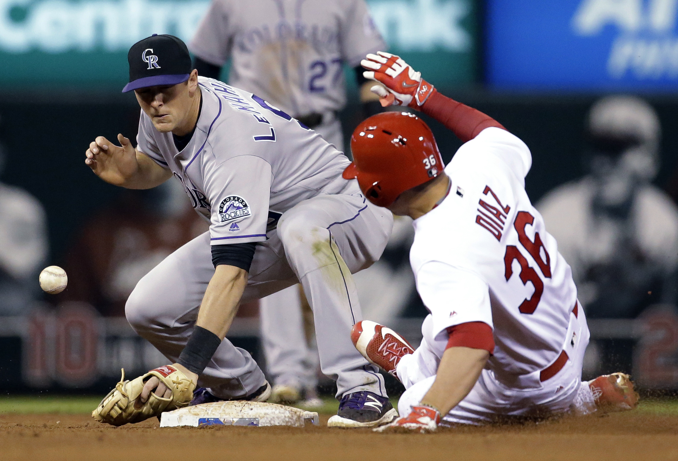 St. Louis Cardinals' Aledmys Diaz, right, is safe at second for a double as the throw gets away from Colorado Rockies second baseman DJ LeMahieu during the sixth inning of a baseball game Wednesday, May 18, 2016, in St. Louis. (AP Photo/Jeff Roberson)