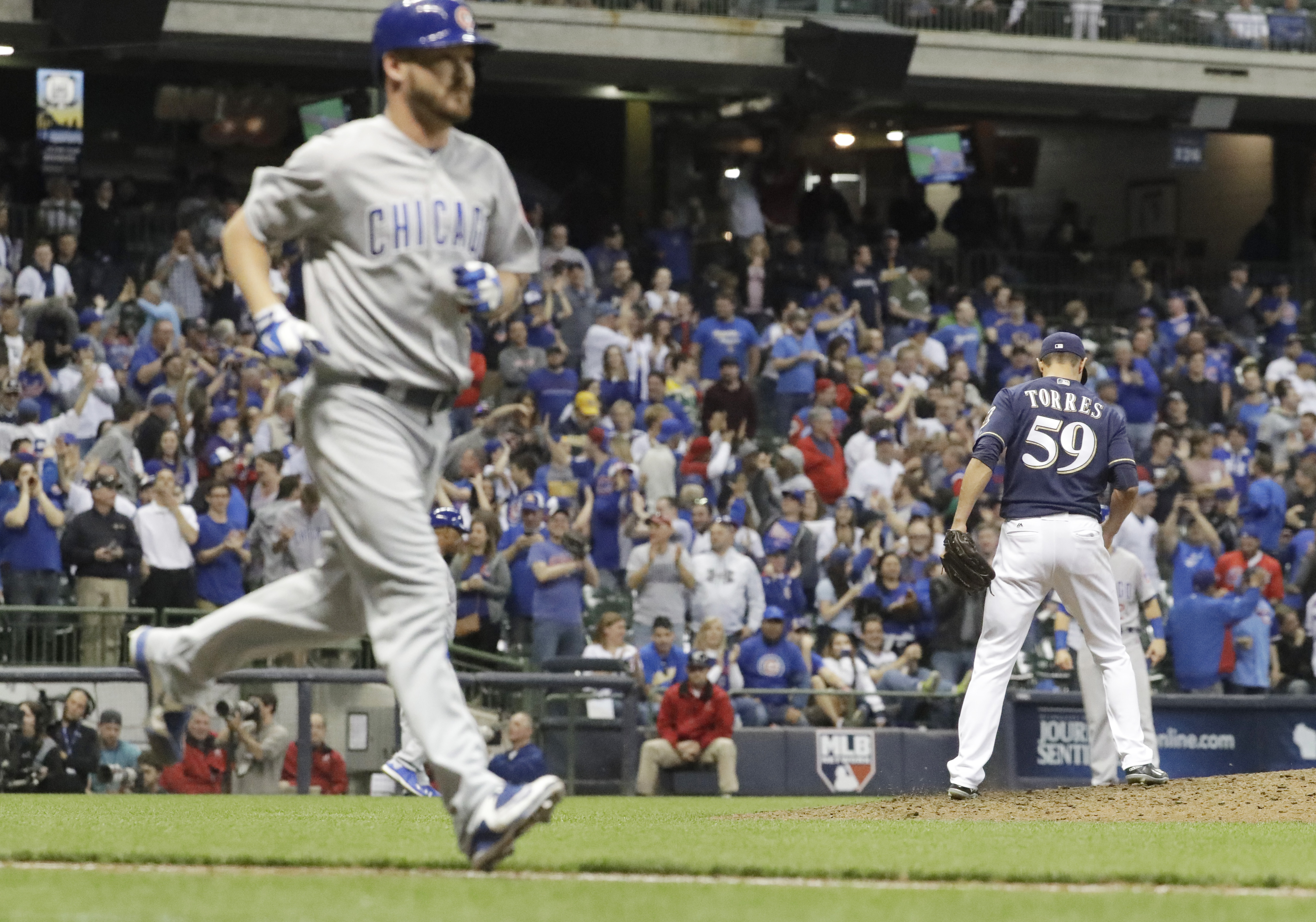 Milwaukee Brewers relief pitcher Carlos Torres sands on the mound as Chicago Cubs' Travis Wood walks to first during the 13th inning of a baseball game Wednesday, May 18, 2016, in Milwaukee. Wood walked with bases loaded. (AP Photo/Morry Gash)