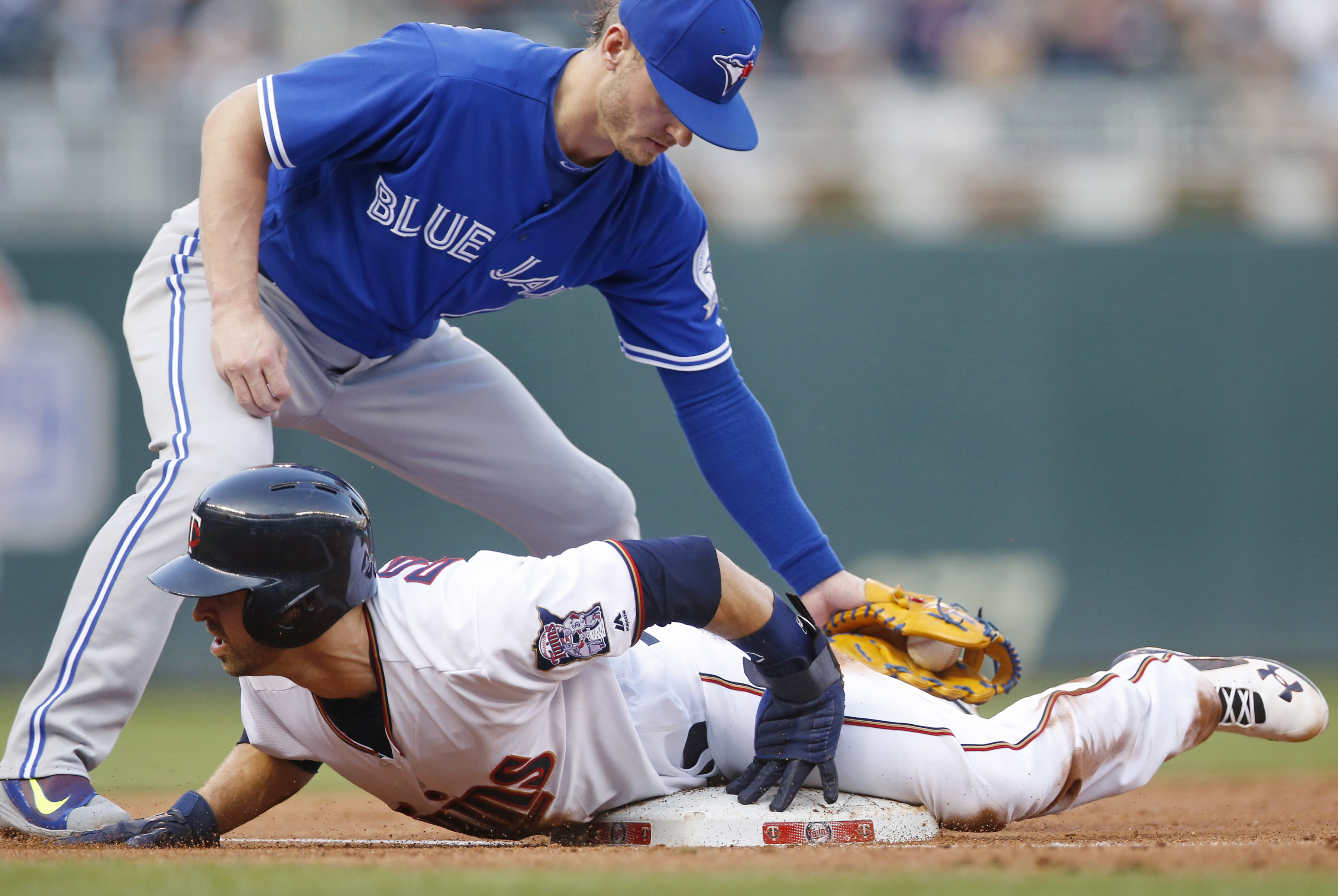 Minnesota Twins' Brian Dozier, bottom, beats the tag by Toronto Blue Jays' Josh Donaldson to advance to third after an error by second baseman Jimmy Paredes during the first inning of a baseball game Thursday, May 19, 2016, in Minneapolis. (AP Photo/Jim M