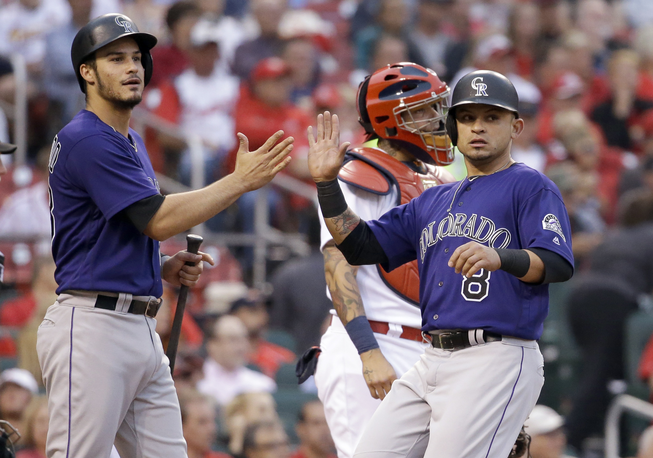 Colorado Rockies' Nolan Arenado, left, and Gerardo Parra, right, score past St. Louis Cardinals catcher Yadier Molina on a single by Daniel Descalso during the fourth inning of a baseball game Thursday, May 19, 2016, in St. Louis. (AP Photo/Jeff Roberson)