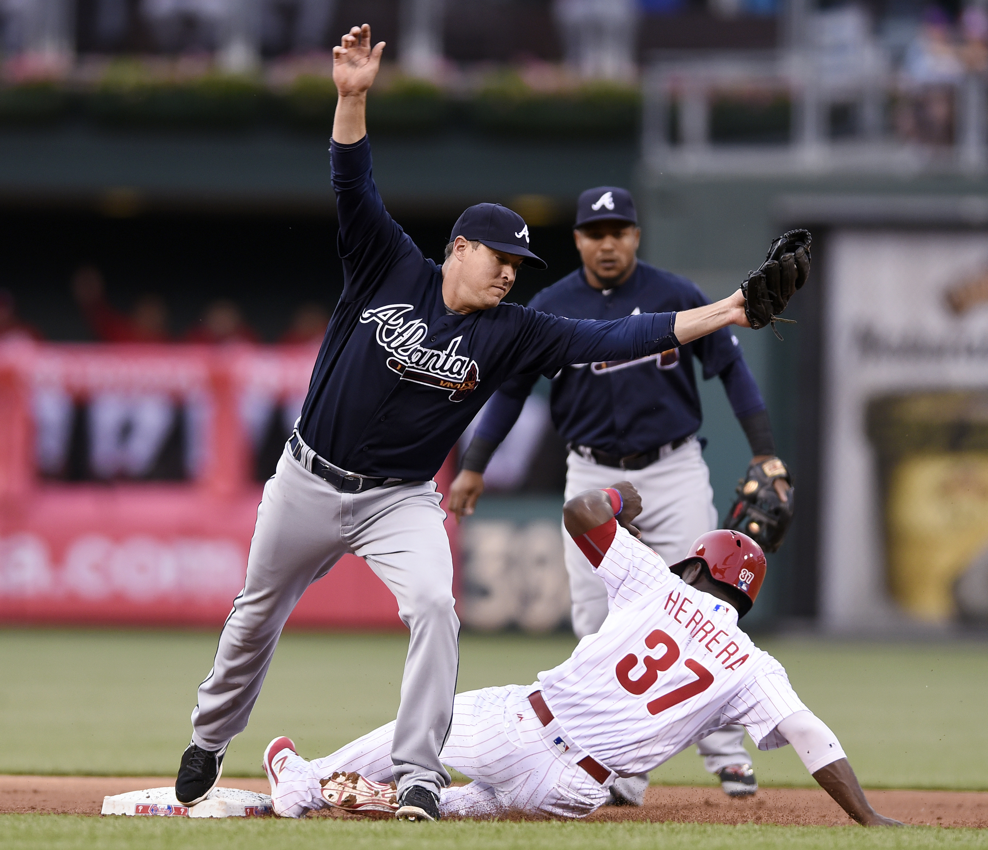 Atlanta Braves second baseman Kelly Johnson avoids colliding with Philadelphia Phillies' Odubel Herrera (37) who is forced out on a Cesar Hernandez ground out in the first inning of a baseball game on Friday, May 20, 2016, in Philadelphia. (AP Photo/Micha