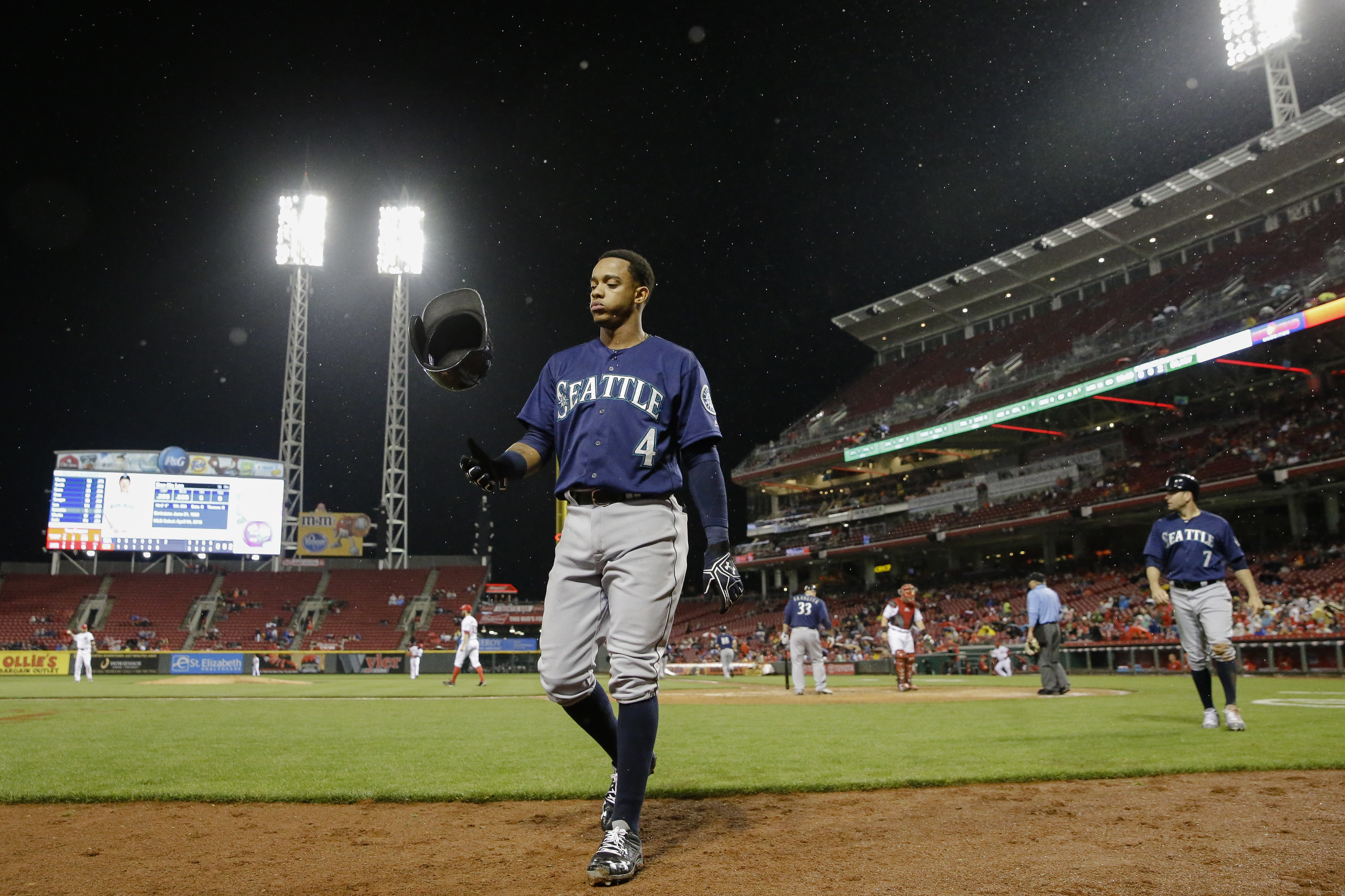 Seattle Mariners' Ketel Marte flips his helmet as he walks to the dugout after scoring on a two-run single by Dae-Ho Lee off Cincinnati Reds relief pitcher Tony Cingrani during the seventh inning of a baseball game, Friday, May 20, 2016, in Cincinnati. (A