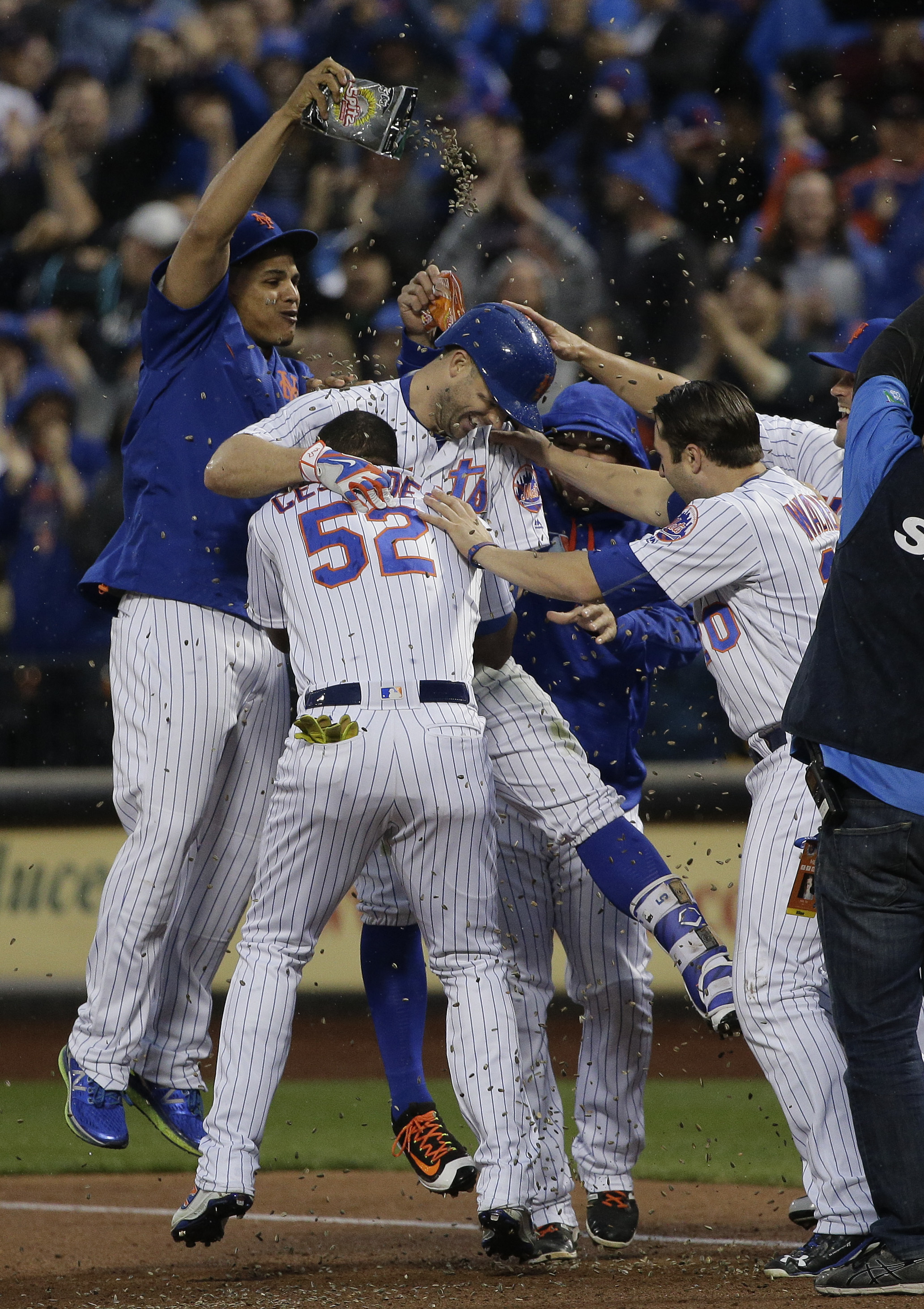 New York Mets' David Wright, center, is showered with sunflower seeds by teammates after driving in the game-winning run with a bases loaded single in the ninth inning of a baseball game against the Milwaukee Brewers, Saturday, May 21, 2016, in New York.