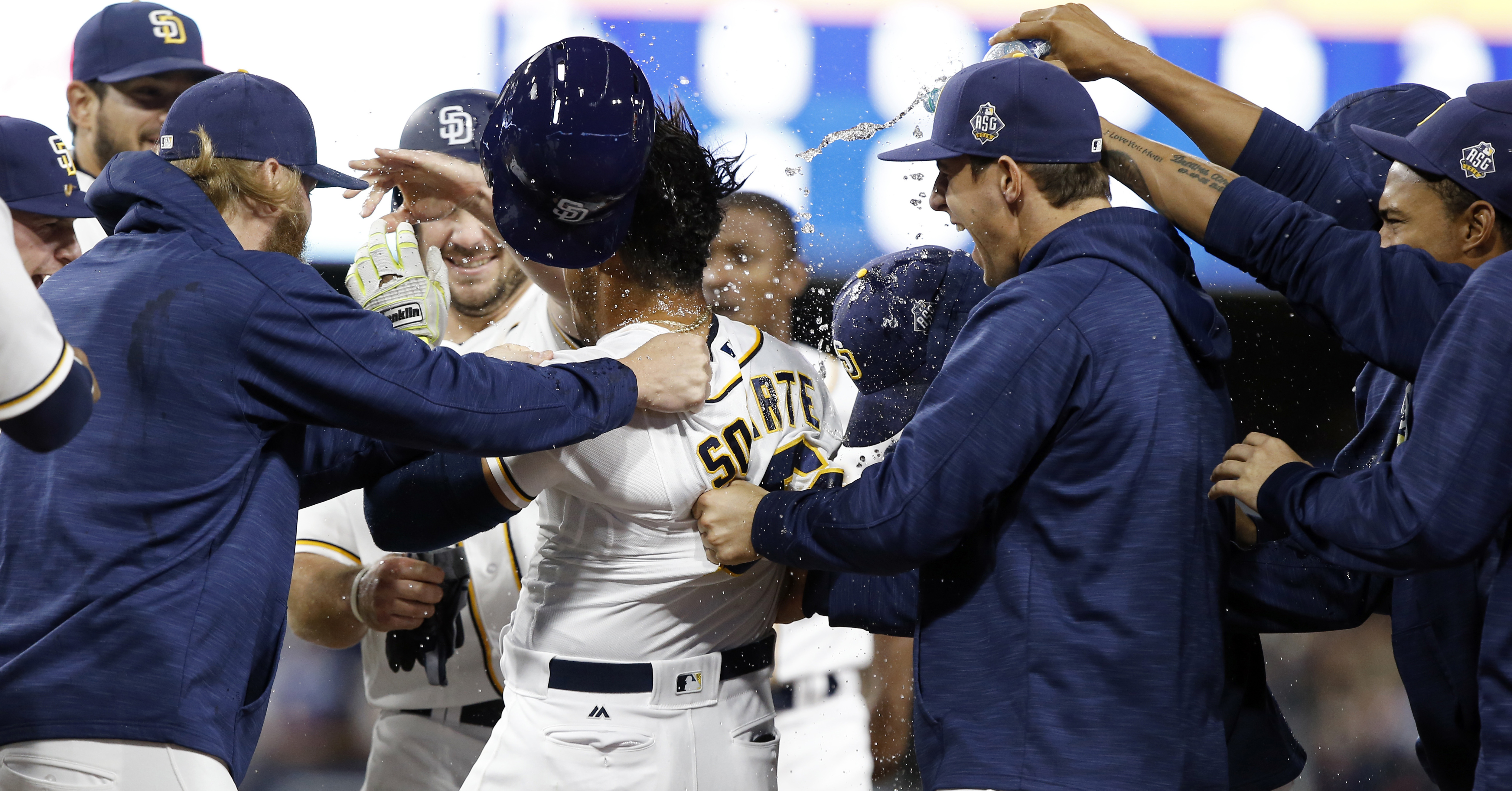 San Diego Padres players celebrate after Yangervis Solarte, center, drew a game winning walk with the bases loaded to score Will Myers to defeat the Los Angeles Dodgers 3-2 in the 11th inning of a baseball game in San Diego, Saturday, May 21, 2016. (AP Ph