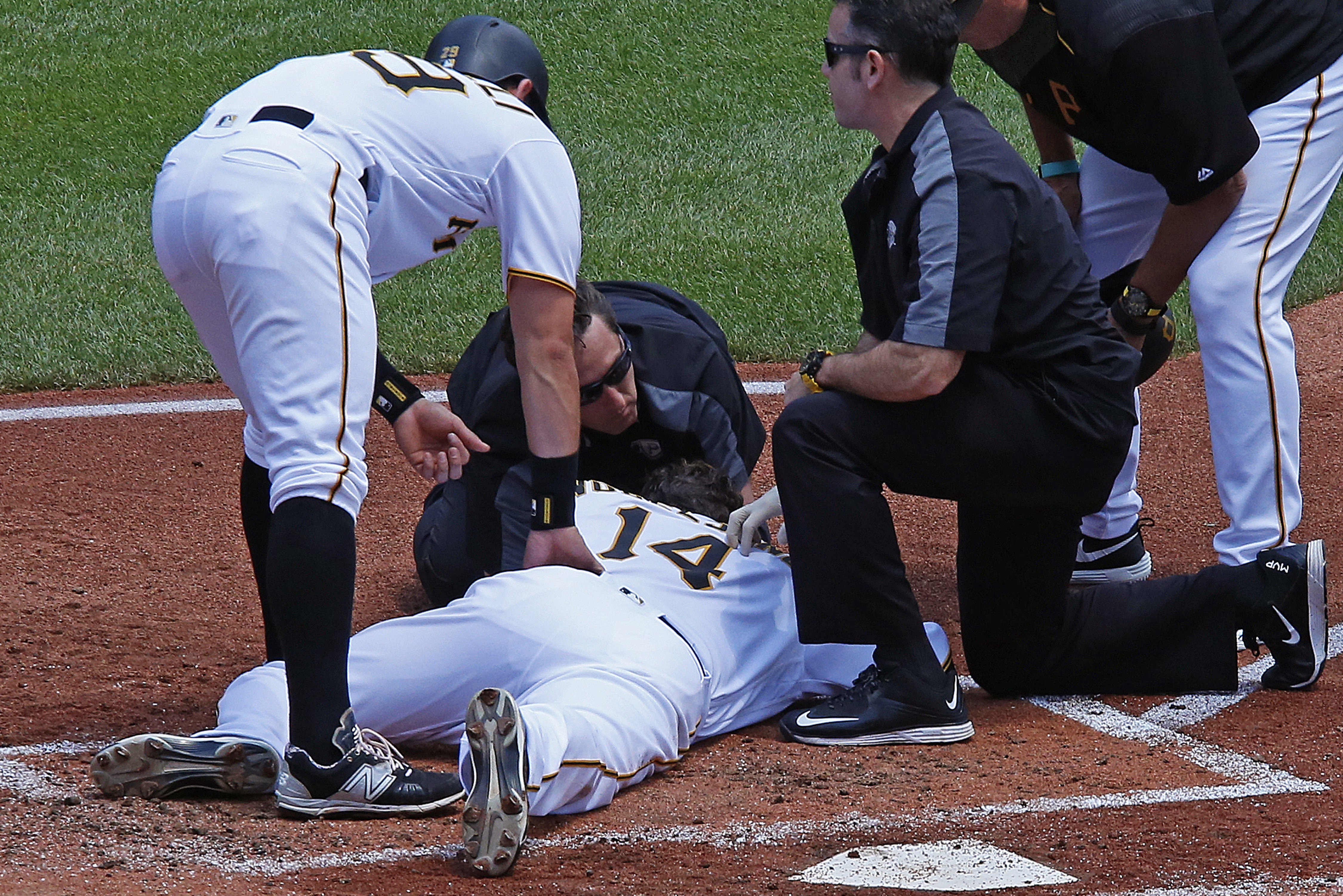 Pittsburgh Pirates pitcher Ryan Vogelsong, center, is helped by team trainers as teammate Francisco Cervelli, left and manager Clint Hurdle, right, look on after being hit in the head by a pitch from starting pitcher Jordan Lyles in the second inning of a