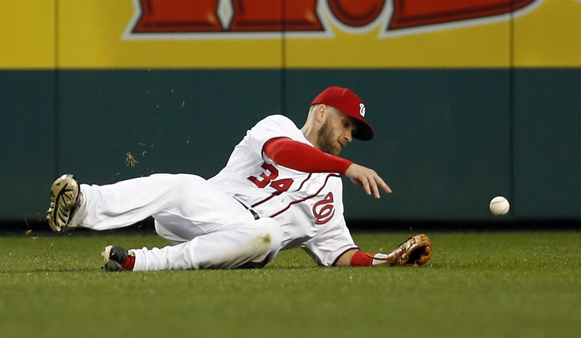 Washington Nationals right fielder Bryce Harper can't catch a ball hit by New York Mets' Curtis Granderson for a single during the first inning of a baseball game at Nationals Park, Monday, May 23, 2016, in Washington. (AP Photo/Alex Brandon)