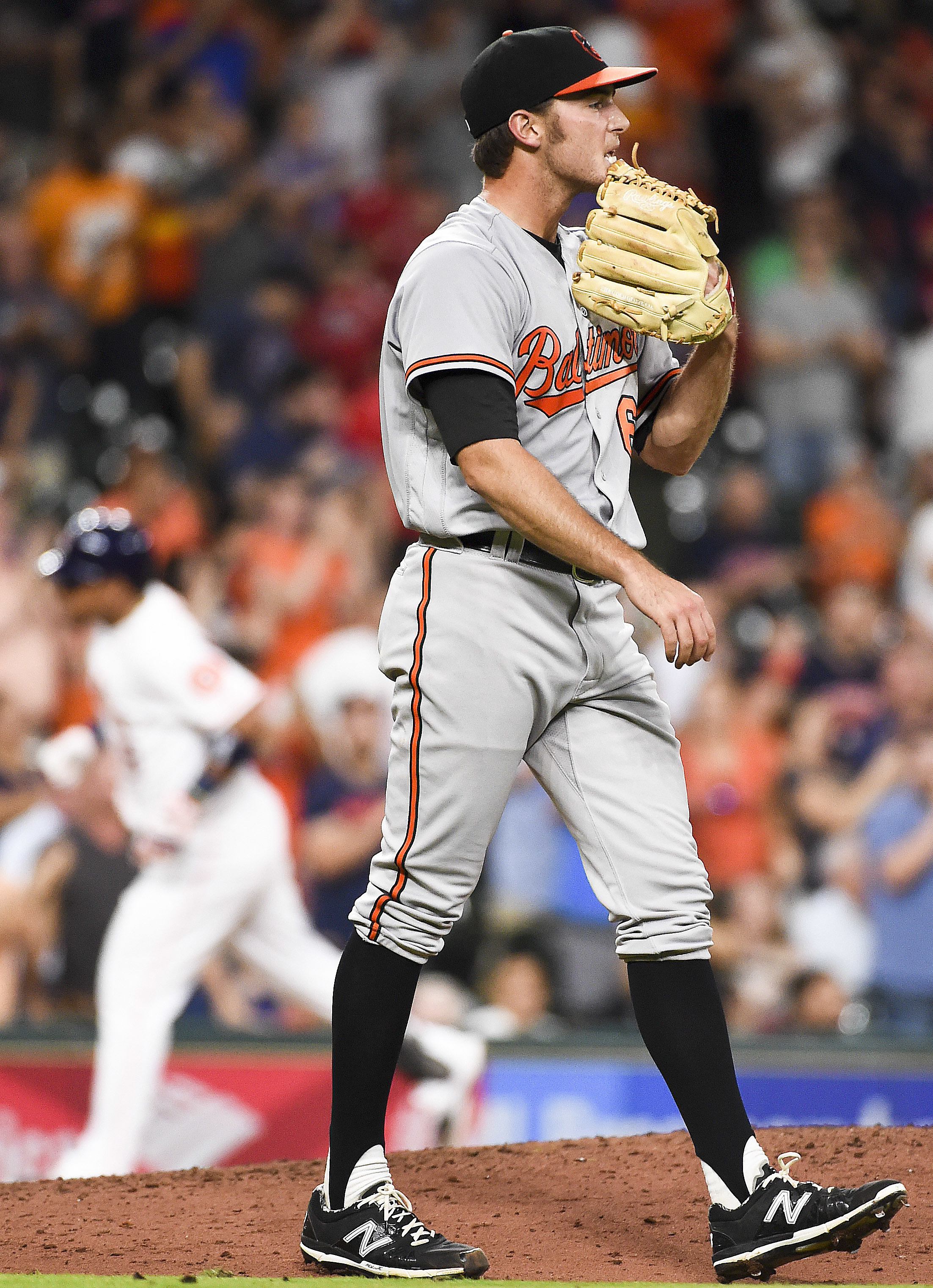 Baltimore Orioles starting pitcher Tyler Wilson, right, looks away as Houston Astros' Luis Valbuena, left, sounds the bases after hitting a two-run home run during the sixth inning of a baseball game, Wednesday, May 25, 2016, in Houston. (AP Photo/Eric Ch
