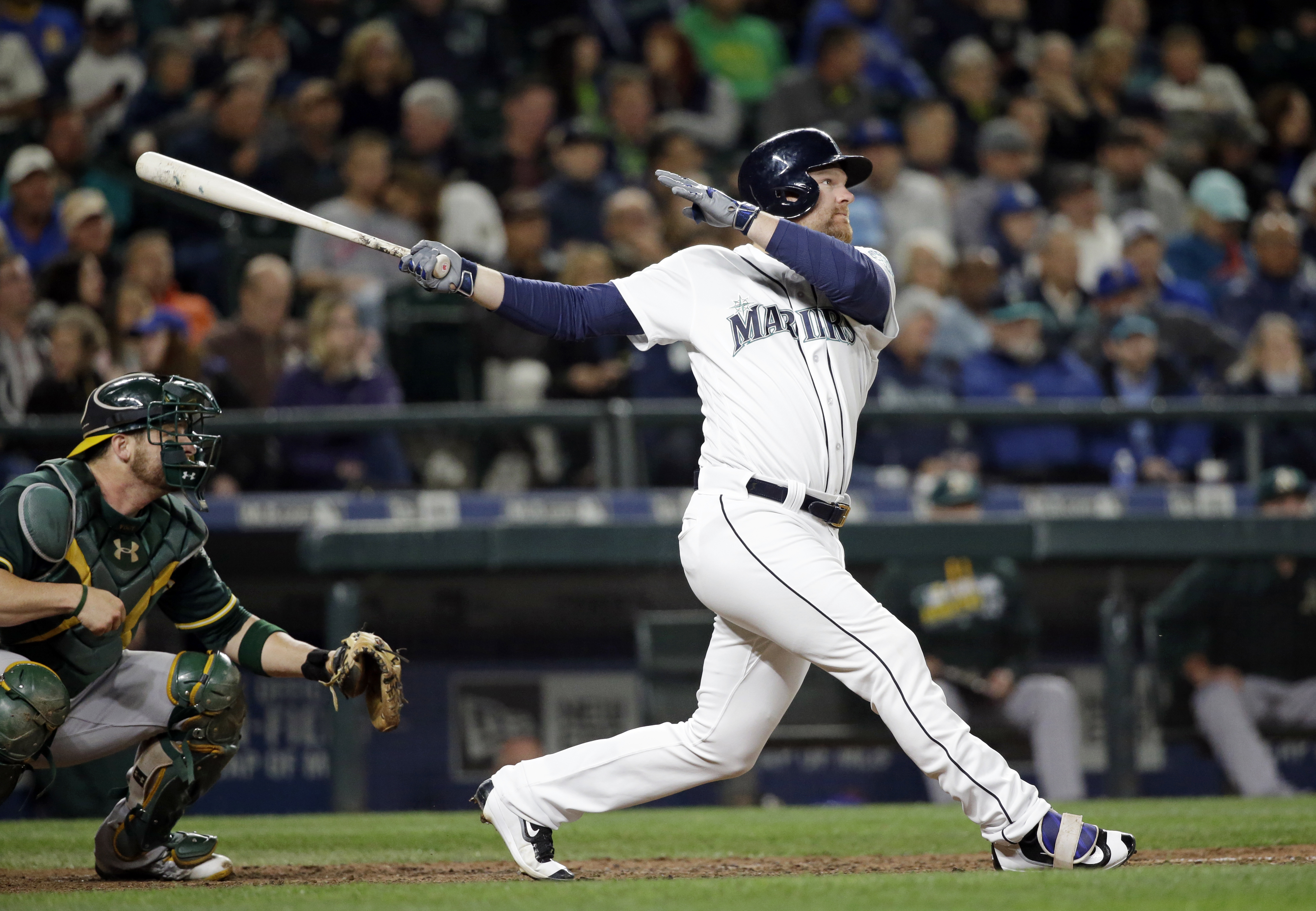 Seattle Mariners' Adam Lind follows through on a double in front of Oakland Athletics catcher Stephen Vogt during the seventh inning of a baseball game Wednesday, May 25, 2016, in Seattle. (AP Photo/Elaine Thompson)