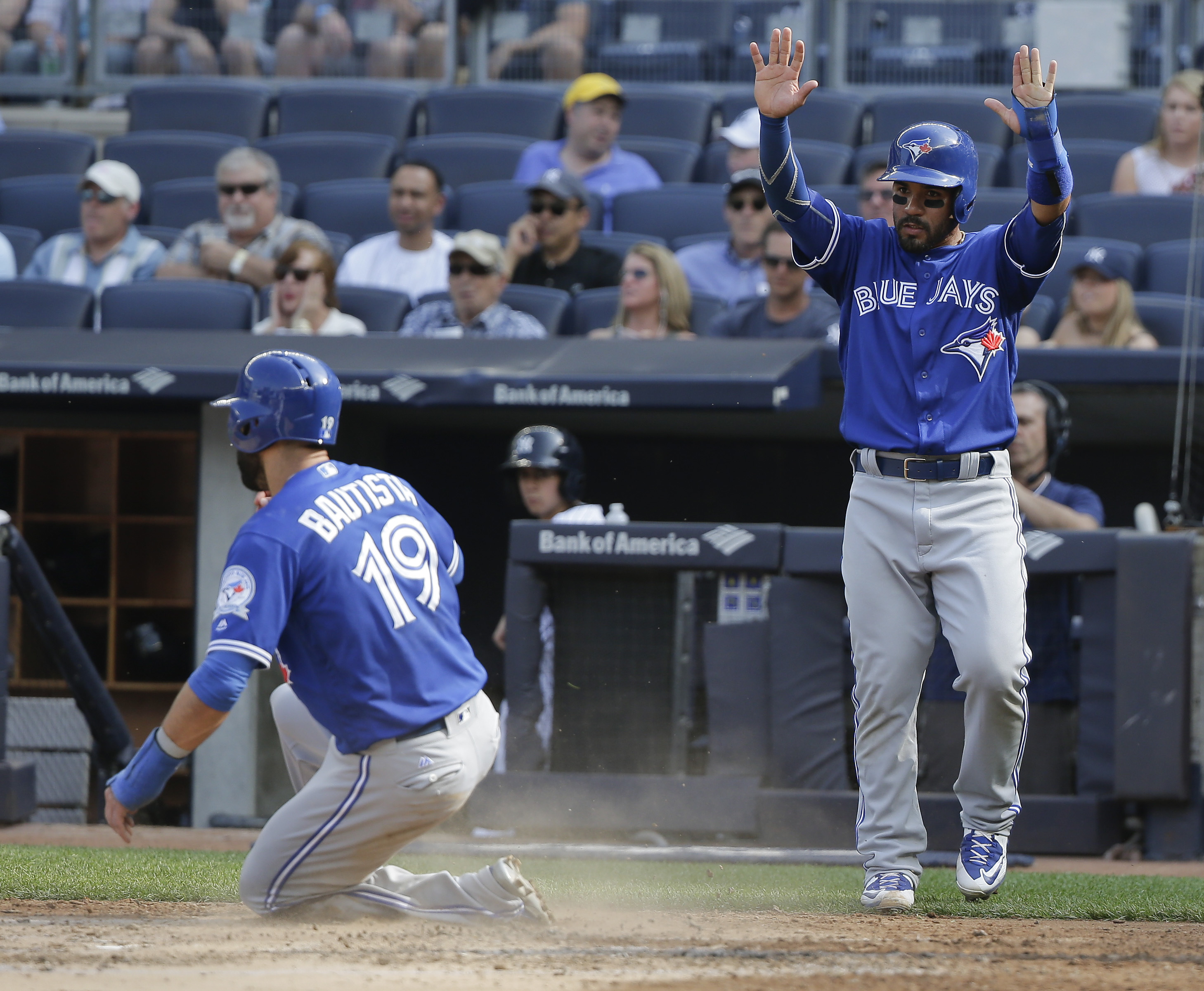 Toronto Blue Jays' Devon Travis, right, raises his hands as Jose Bautista (19) scores on a base hit by designated hitter Edwin Encarnacion during the third inning of a baseball game against the New York Yankees, Thursday, May 26, 2016, in New York. (AP Ph