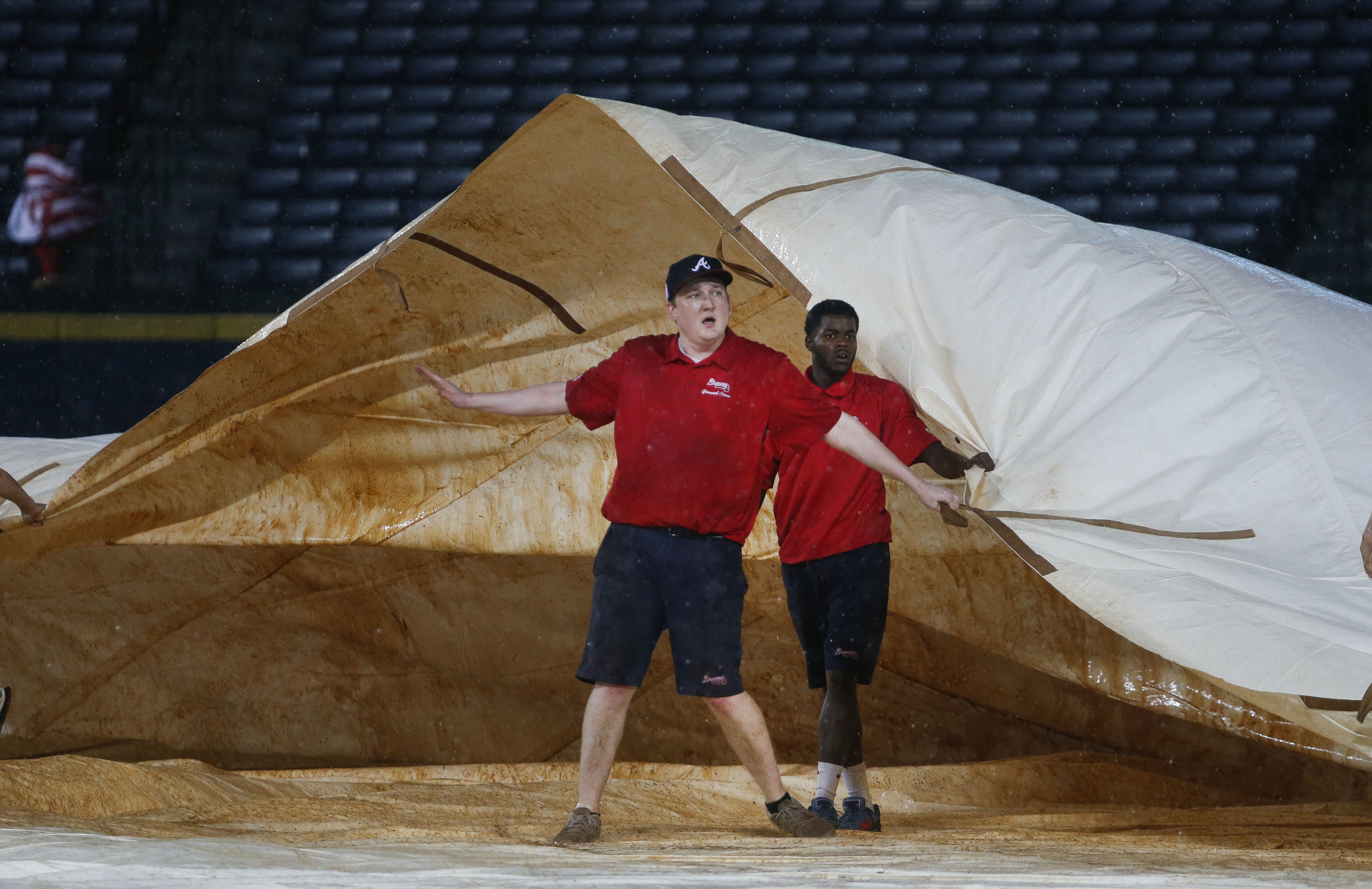Members of the Atlanta Braves grounds crew work to cover the infield during a rain delay in the seventh inning of the Braves' baseball game against the Milwaukee Brewers on Thursday, May 26, 2016, in Atlanta. (AP Photo/John Bazemore)
