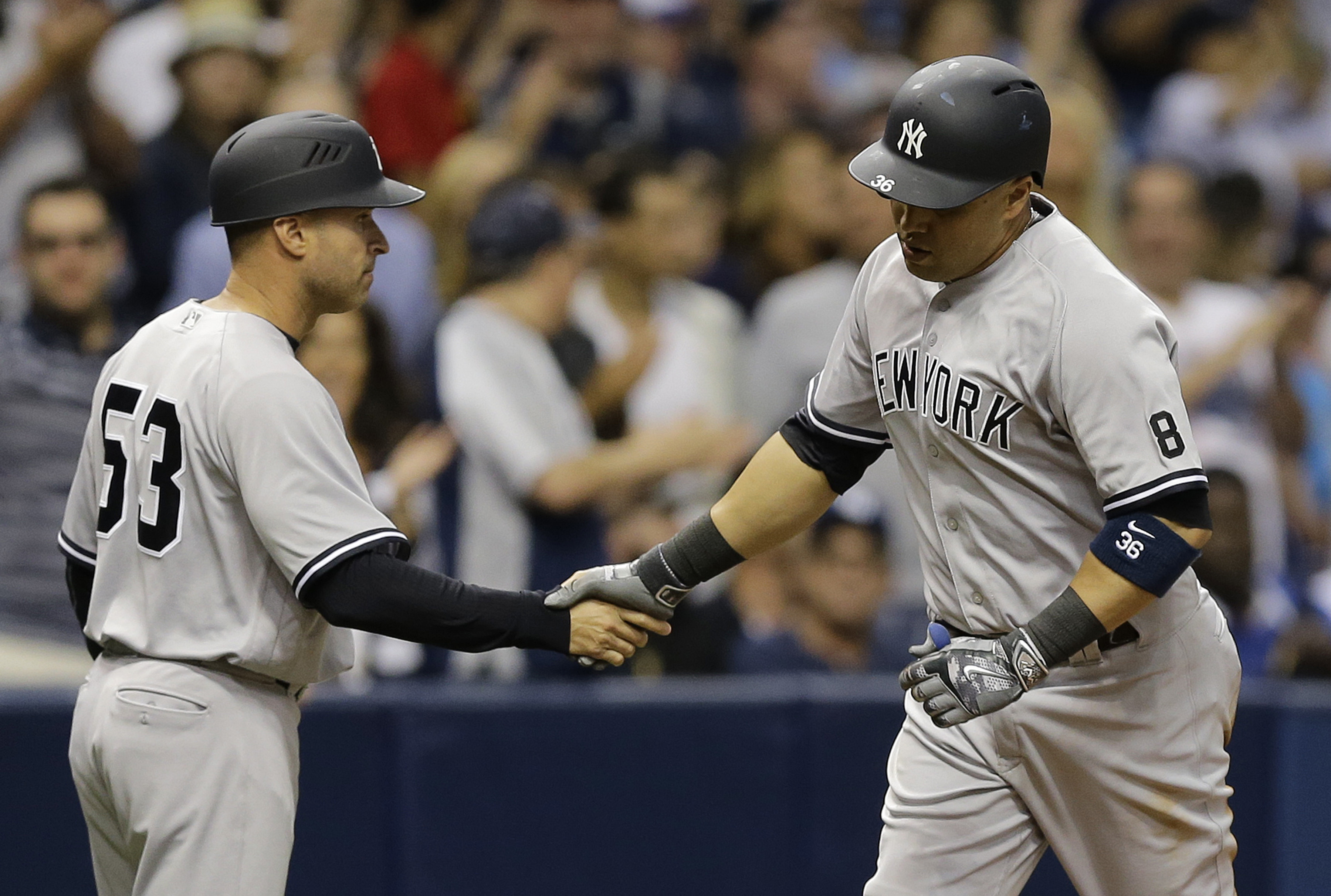 New York Yankees' Carlos Beltran, right, shakes hands with third base coach Joe Espada after hitting a home run off Tampa Bay Rays starting pitcher Chris Archer during the eighth inning of a baseball game Friday, May 27, 2016, in St. Petersburg, Fla. (AP