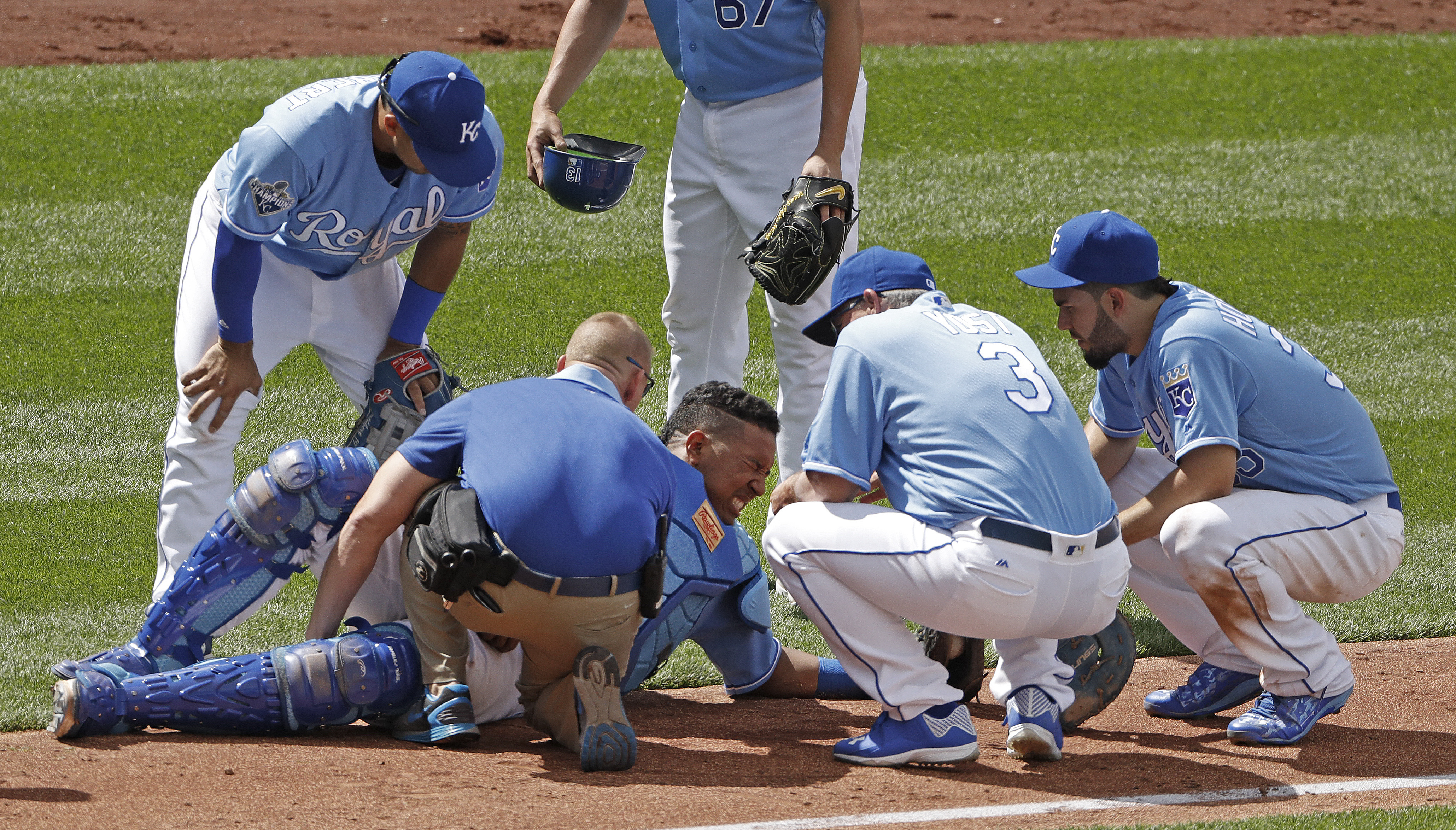 Kansas City Royals catcher Salvador Perez, center, is tended to after a collision following his catch of a fly foul ball for the out on Chicago White Sox's Adam Eaton during the ninth inning of a baseball game Saturday, May 28, 2016, in Kansas City, Mo. T