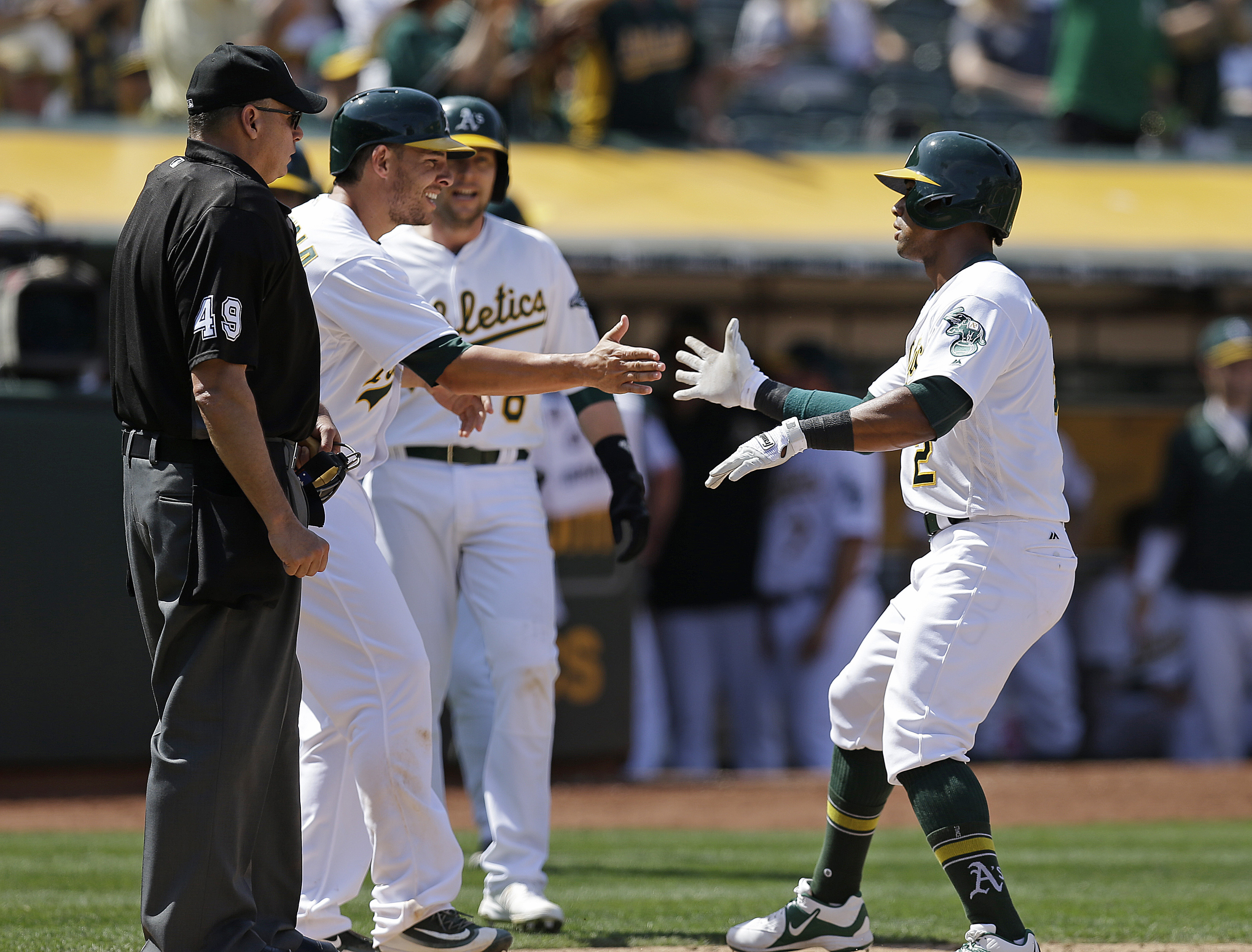 Oakland Athletics' Khris Davis, right, is congratulated by Danny Valencia after hitting a three-run home run off Detroit Tigers' Alex Wilson in the seventh inning of a baseball game Saturday, May 28, 2016, in Oakland, Calif. Home plate umpire Andy Fletche
