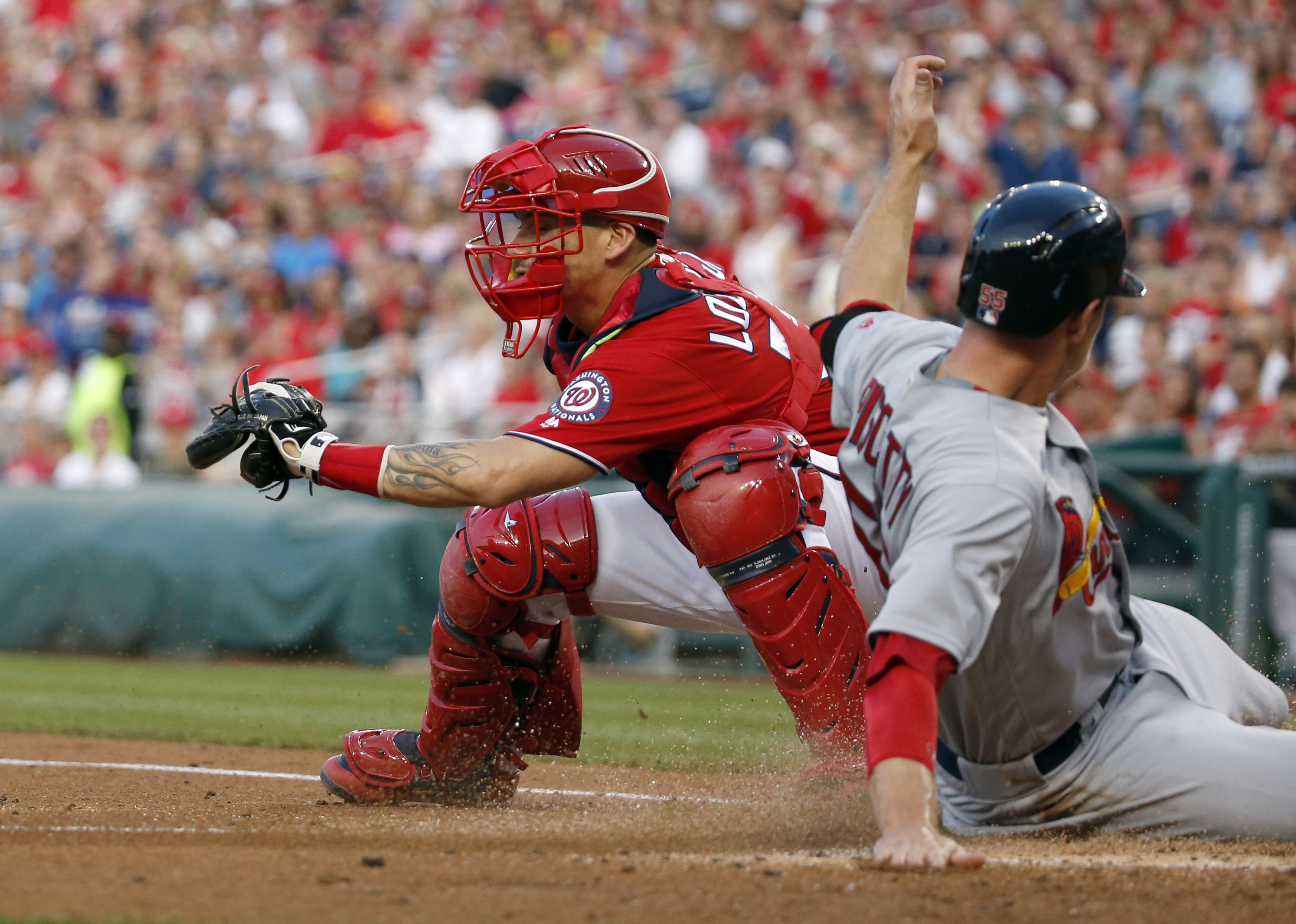 St. Louis Cardinals' Stephen Piscotty, right, slides safely into home as Washington Nationals catcher Jose Lobaton cannot make the tag in time after a single by Cardinals' Greg Garcia during the second inning of a baseball game at Nationals Park, Saturday