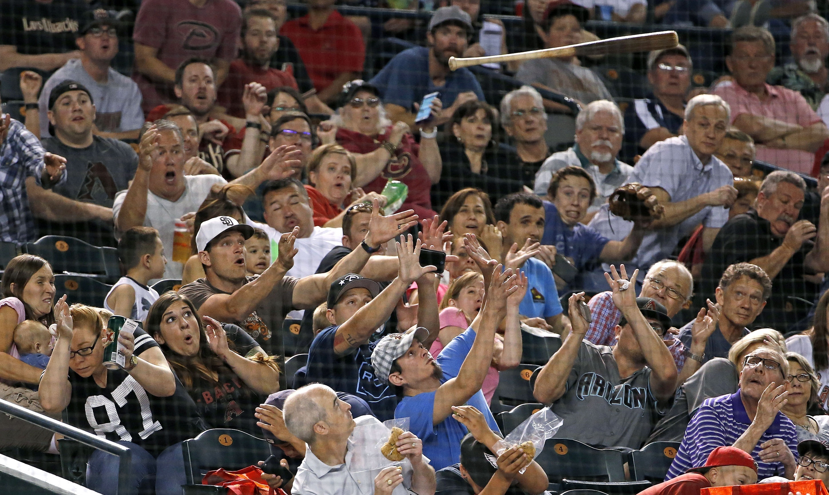 Fans show a variety of reactions after San Diego Padres' Derek Norris lost control of his bat and it flew toward the stands during the fifth inning of the Padres' baseball game against the Arizona Diamondbacks on Saturday, May 28, 2016, in Phoenix. (AP Ph