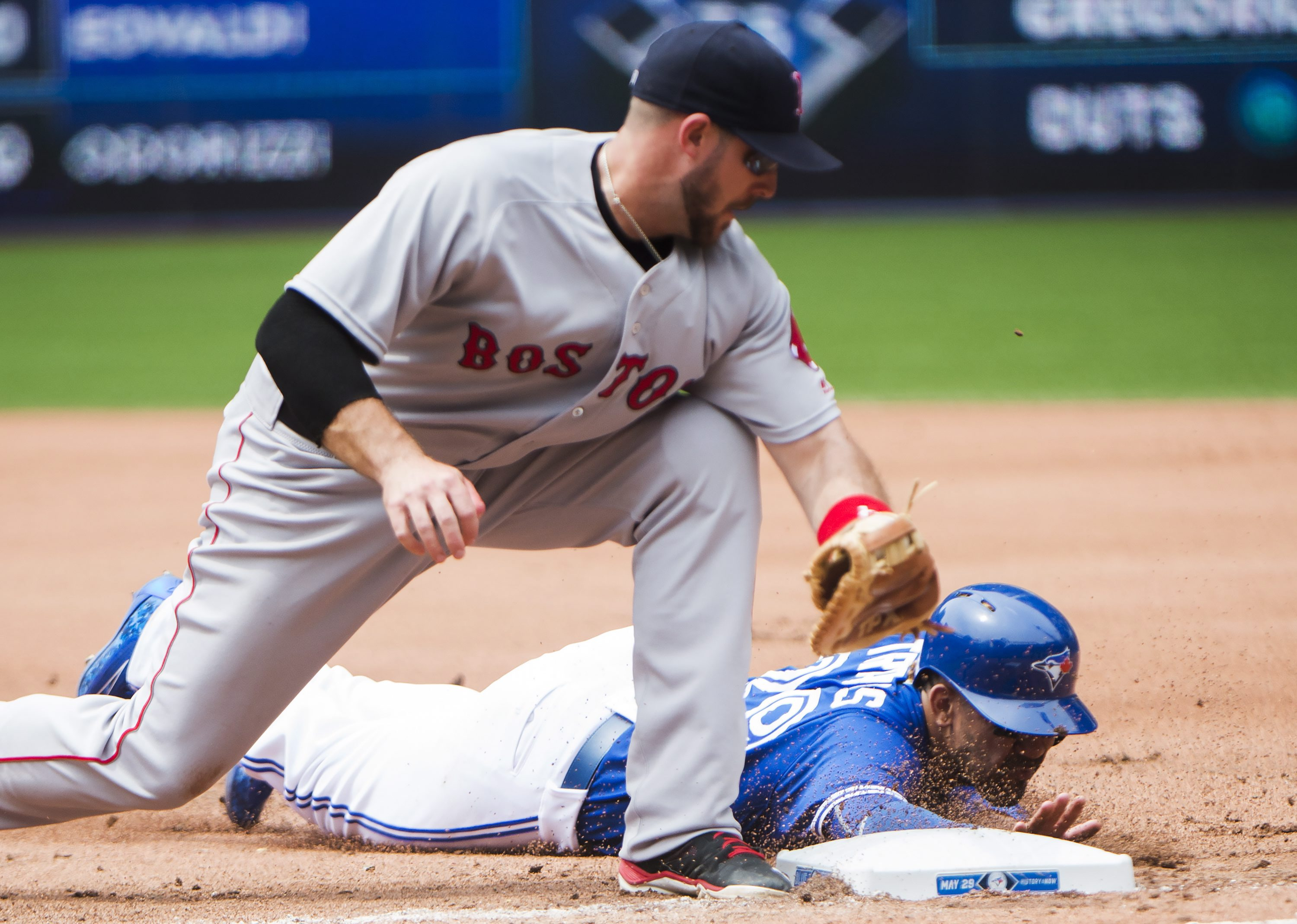 Toronto Blue Jays' Devon Travis (29) gets back to first base safely under the tag of Boston Red Sox first baseman Travis Shaw during fourth-inning baseball game action in Toronto on Sunday, May 29, 2016. (Nathan Denette/The Canadian Press via AP) MANDATOR