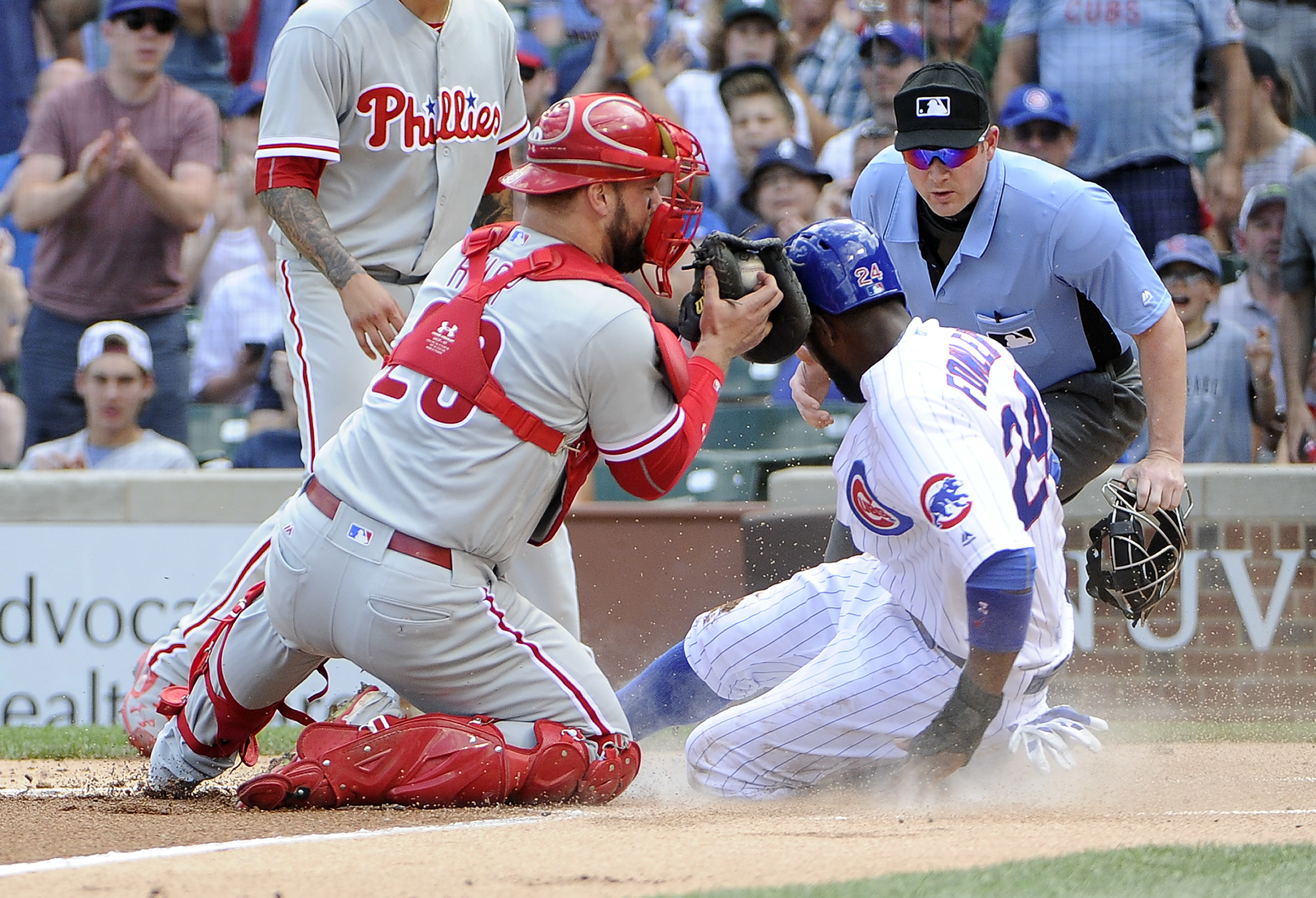 Chicago Cubs' Dexter Fowler (24) is safe at home as Philadelphia Phillies catcher Cameron Rupp (29) makes a late tag during the first inning of a baseball game, Sunday, May 29, 2016, in Chicago. (AP Photo/David Banks)