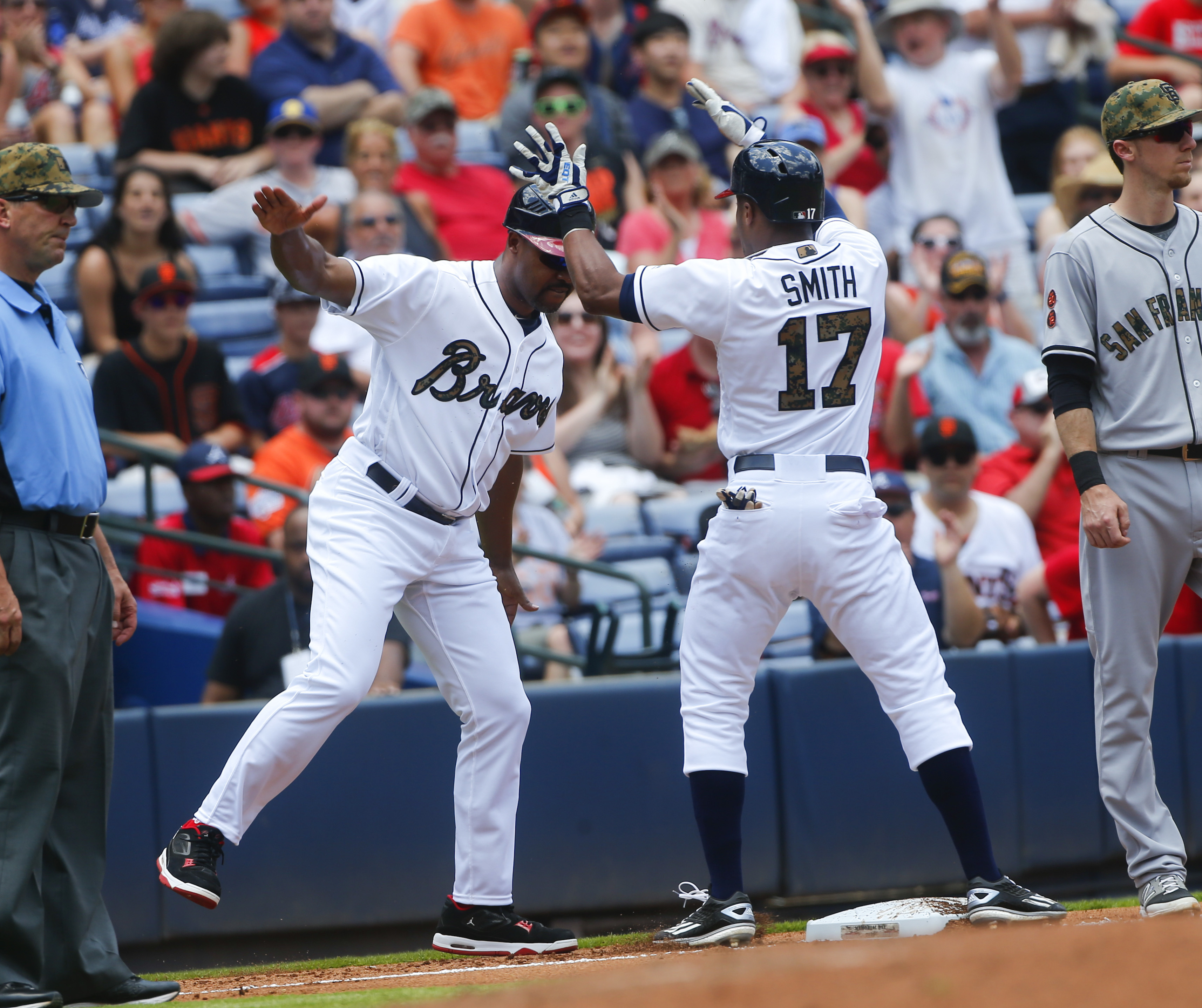 Atlanta Braves' Mallex Smith (17) celebrates with third base coach Bo Porter after a three-run triple in the second inning of a baseball game against the San Francisco Giants Monday, May 30, 2016, in Atlanta. (AP Photo/John Bazemore)