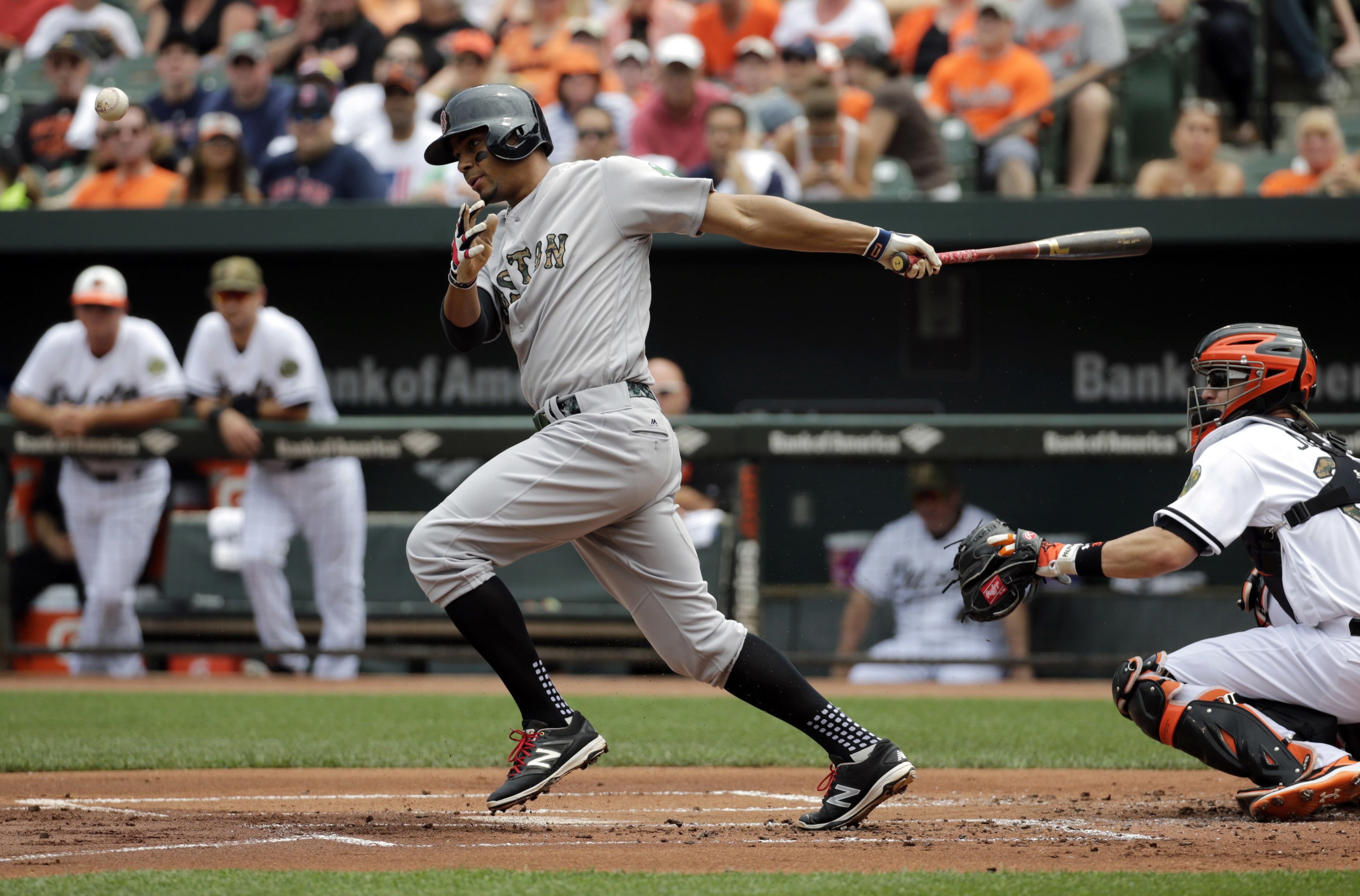 Boston Red Sox's Xander Bogaerts hits a sacrifice ground ball in front of Baltimore Orioles catcher Caleb Joseph in the first inning of a baseball game in Baltimore, Monday, May 30, 2016. Mookie Betts scored on the play. (AP Photo/Patrick Semansky)