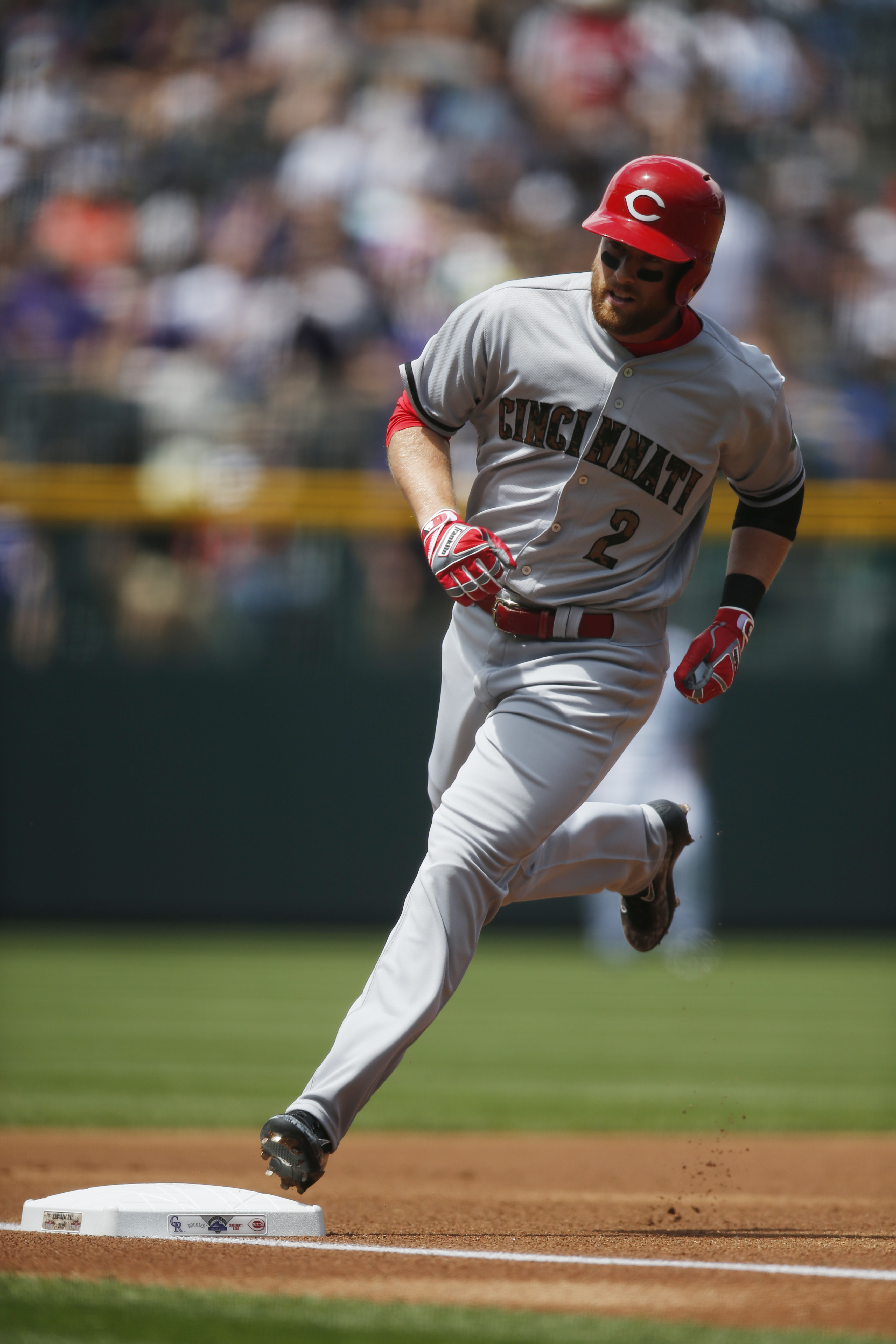Cincinnati Reds' Zack Cozart circles the bases after hitting a solo home run on the first pitch from Colorado Rockies starting pitcher Chad Bettis in the first inning of a baseball game Monday, May 30, 2016, in Denver. (AP Photo/David Zalubowski)