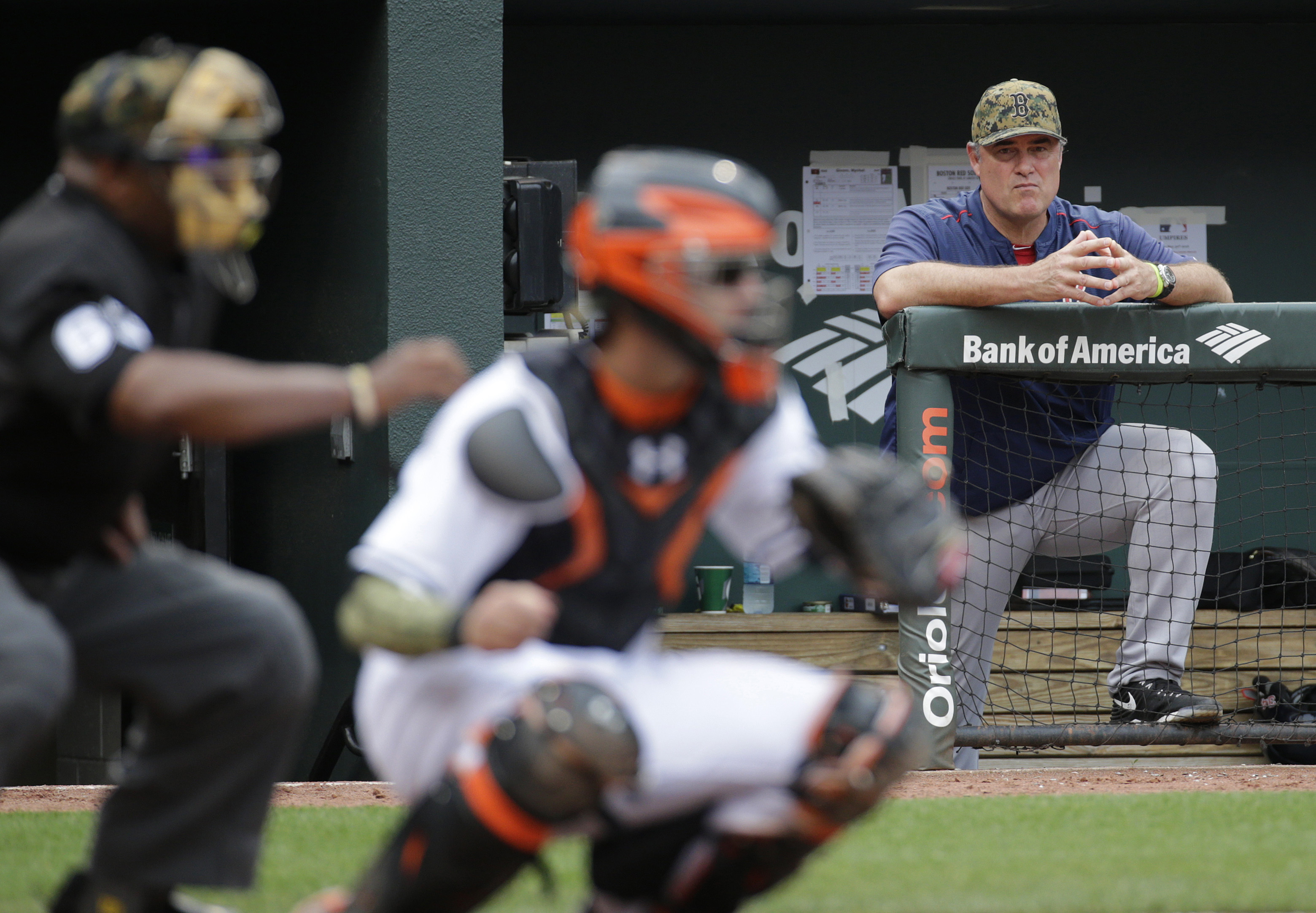 Boston Red Sox manager John Farrell, back right, is seen past home plate umpire Laz Diaz, left, and Baltimore Orioles catcher Caleb Joseph as he watches from the dugout in the ninth inning of a baseball game in Baltimore, Monday, May 30, 2016. (AP Photo/P