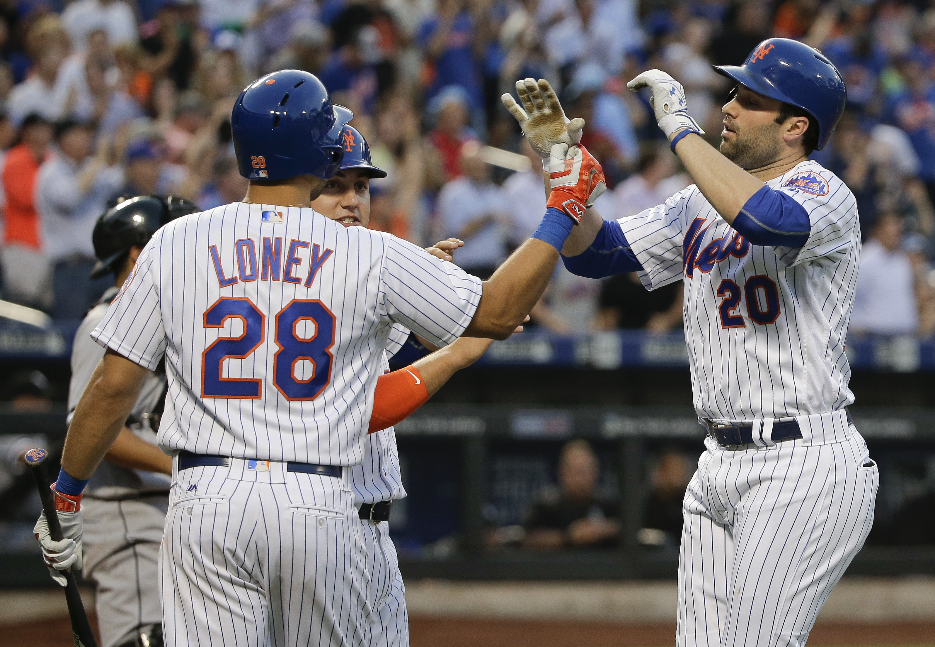 New York Mets' Neil Walker (20) is greeted at home plate by James Loney (28) and Michael Conforto after hitting a two-run home run against the Chicago White Sox during the third inning of a baseball game, Tuesday, May 31, 2016, in New York. (AP Photo/Juli
