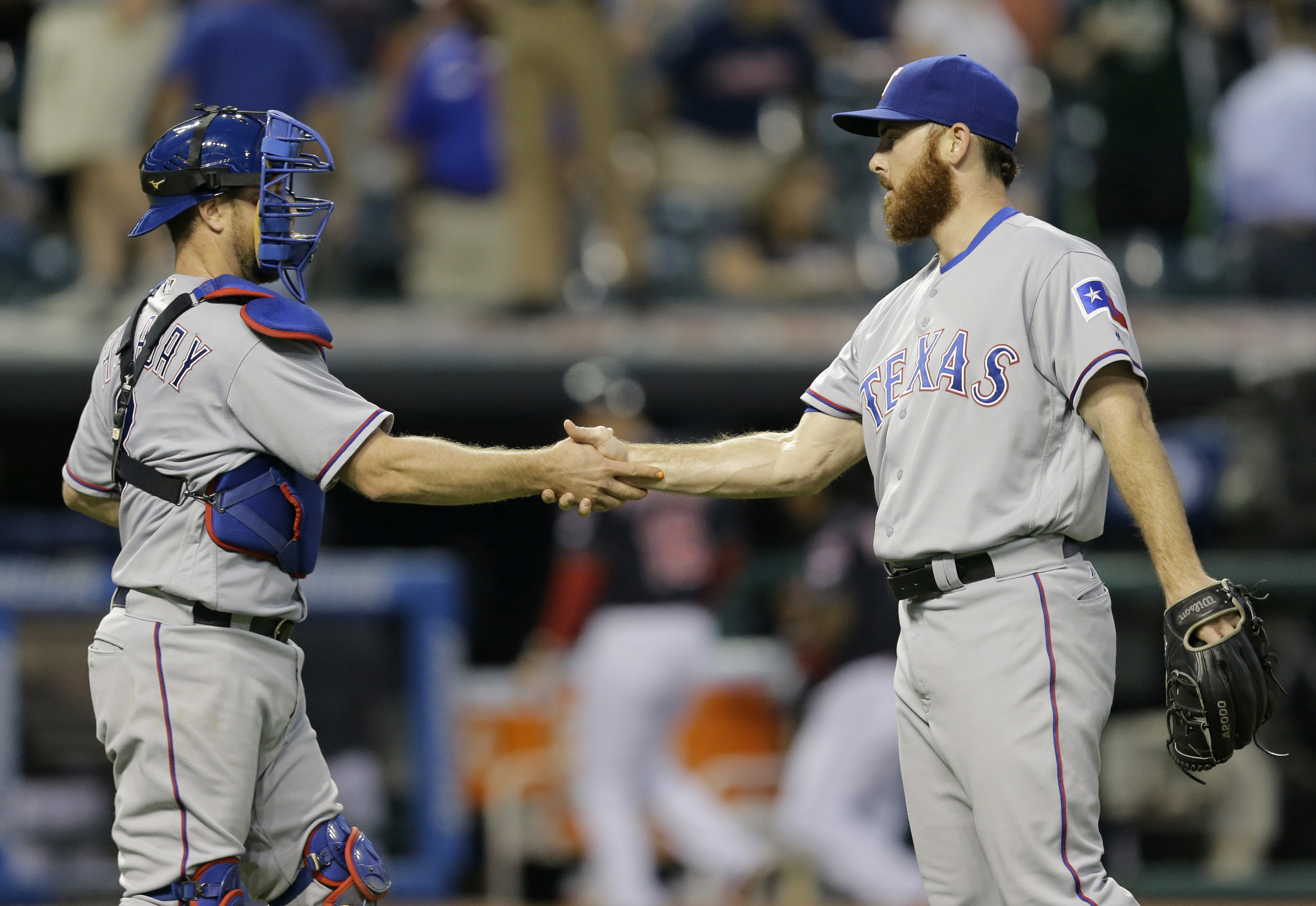 Texas Rangers relief pitcher Sam Dyson, right, and catcher Bryan Holaday celebrate after the Rangers defeated the Cleveland Indians 7-3 in a baseball game, Tuesday, May 31, 2016, in Cleveland. (AP Photo/Tony Dejak)