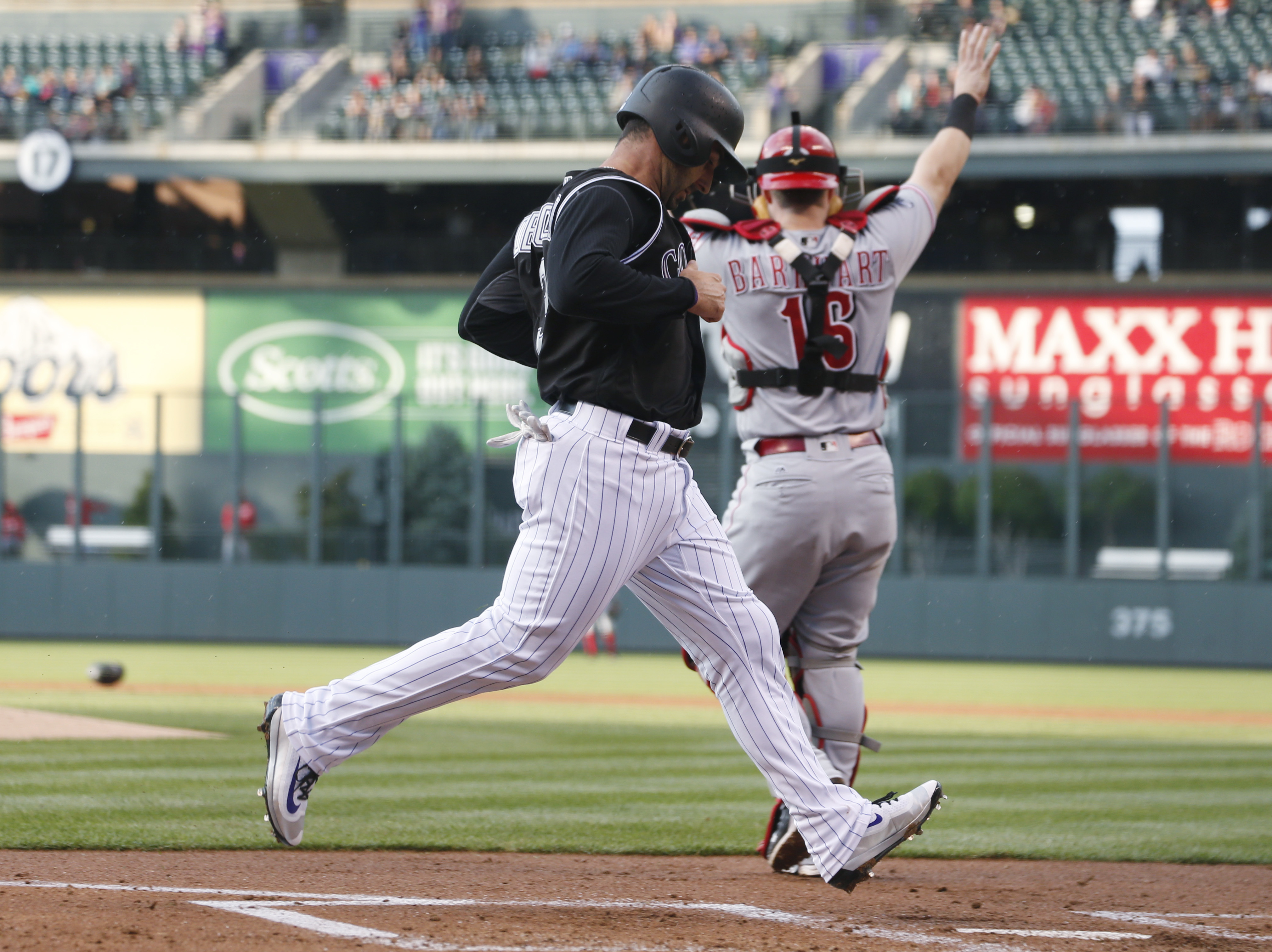 Colorado Rockies' Daniel Descalso, scores on a double by Tony Wolters as Cincinnati Reds catcher Tucker Barnhart looks for the throw in the first inning of a baseball game Tuesday, May 31, 2016, in Denver. (AP Photo/David Zalubowski)