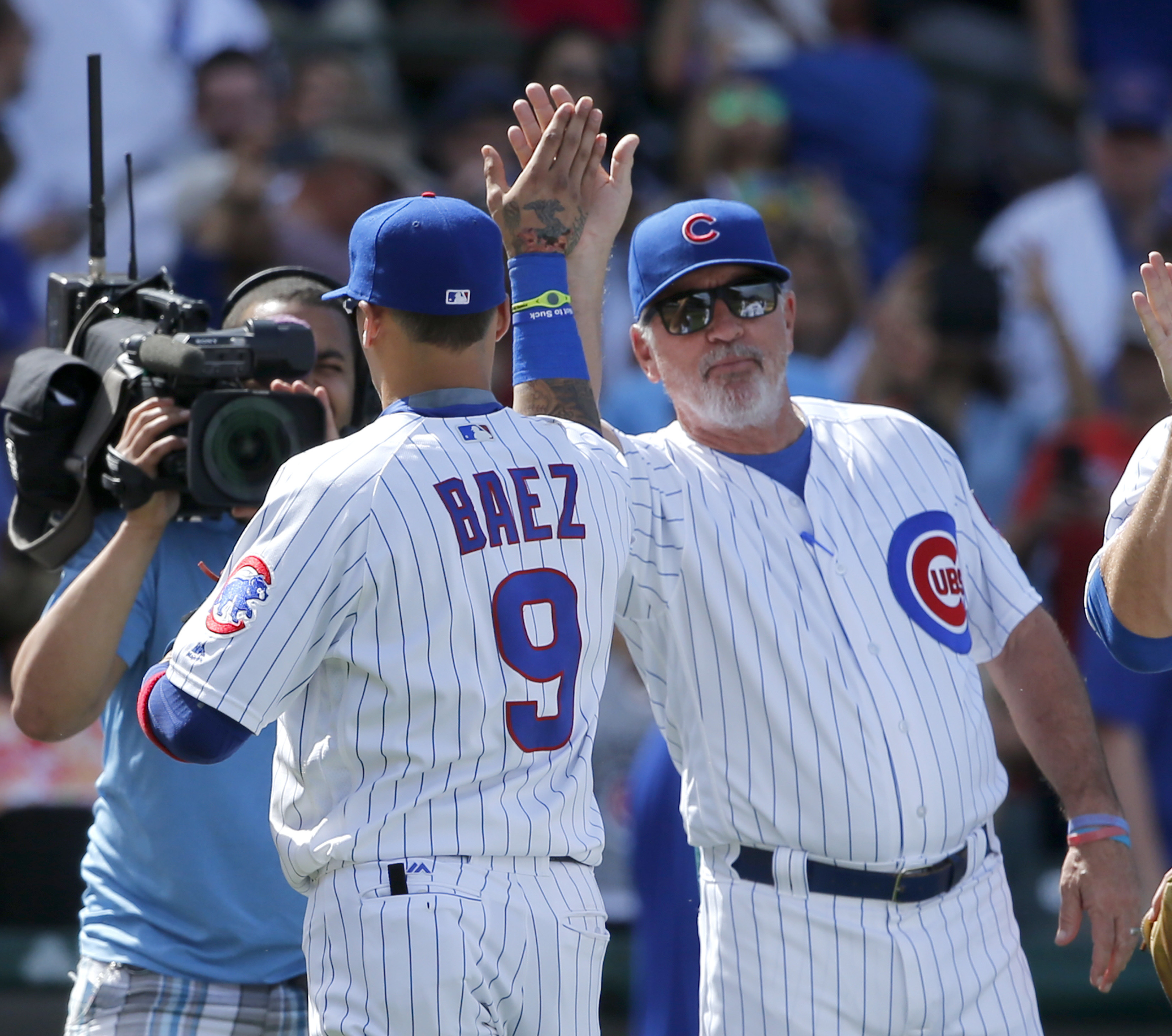Chicago Cubs manager Joe Maddon, right, and Javier Baez celebrate the Cubs' 7-2 win over the Los Angeles Dodgers after a baseball game Thursday, June 2, 2016, in Chicago. (AP Photo/Charles Rex Arbogast)