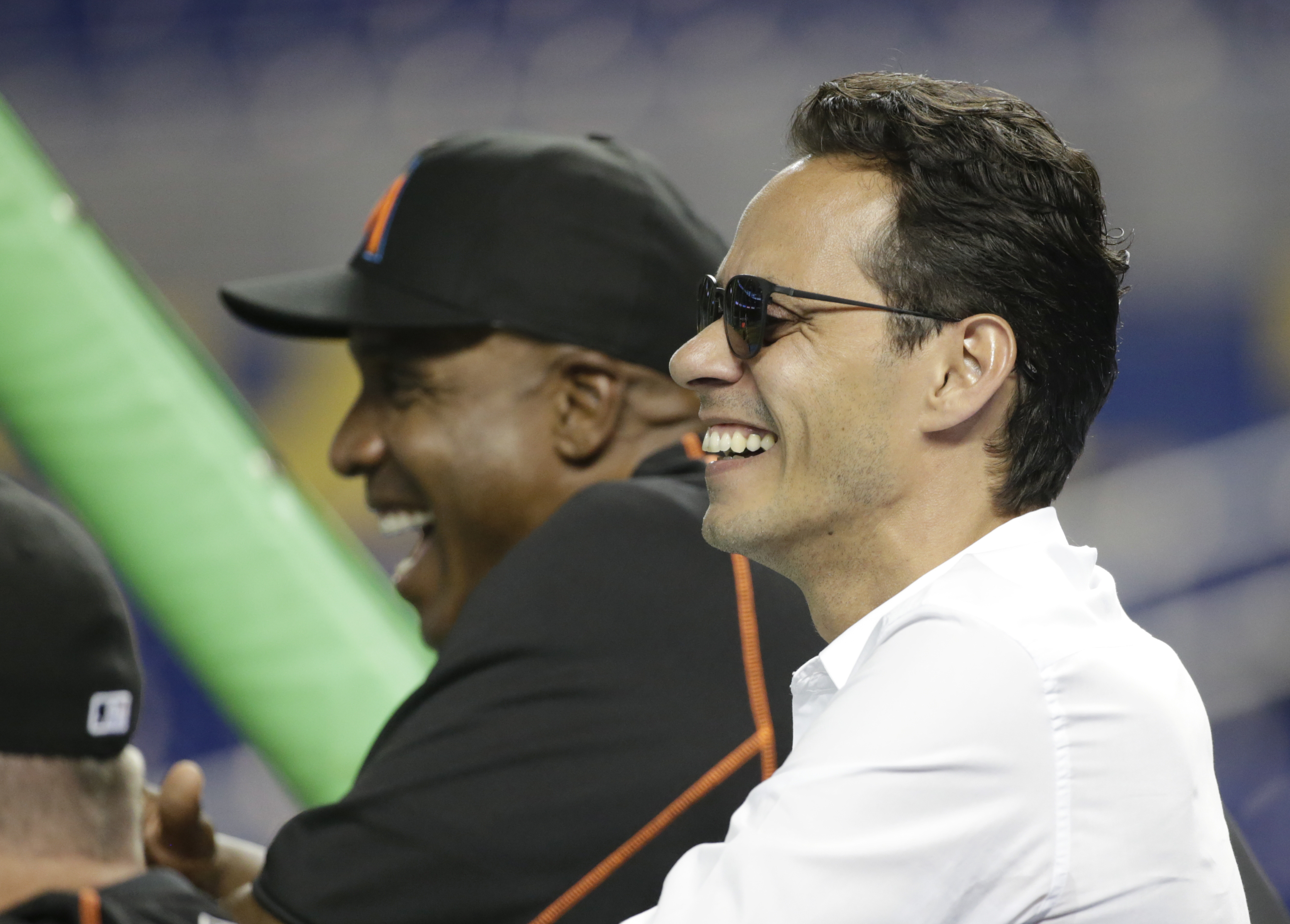 Entertainer Marc Anthony, foreground, watches Miami Marlins batting practice with hitting coach Barry Bonds, rear, before the start of a baseball game between the Miami Marlins and the New York Mets, Friday, June 3, 2016, in Miami. (AP Photo/Wilfredo Lee)