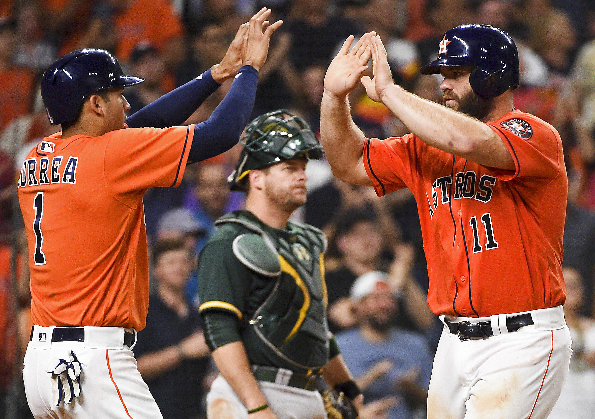Houston Astros' Evan Gattis (11) celebrates his two-run home run off Oakland Athletics relief pitcher Andrew Triggs with Carlos Correa (1) during the fourth inning of a baseball game, Friday, June 3, 2016, in Houston. (AP Photo/Eric Christian Smith)