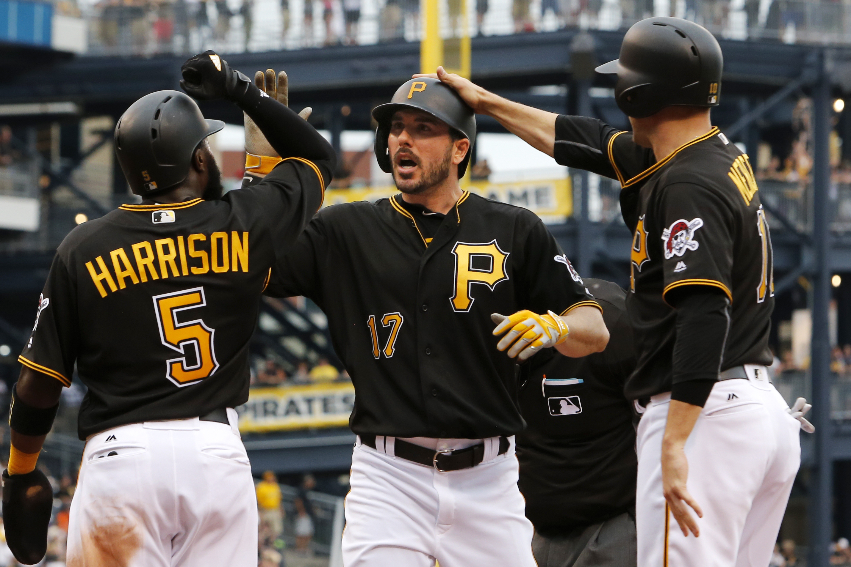 Pittsburgh Pirates' Matt Joyce (17) is greeted by teammates Josh Harrison (5) and Jordy Mercer who were on base for his three-run home run during the seventh inning of a baseball game Los Angeles Angles in Pittsburgh, Saturday, June 4, 2016. (AP Photo/Gen