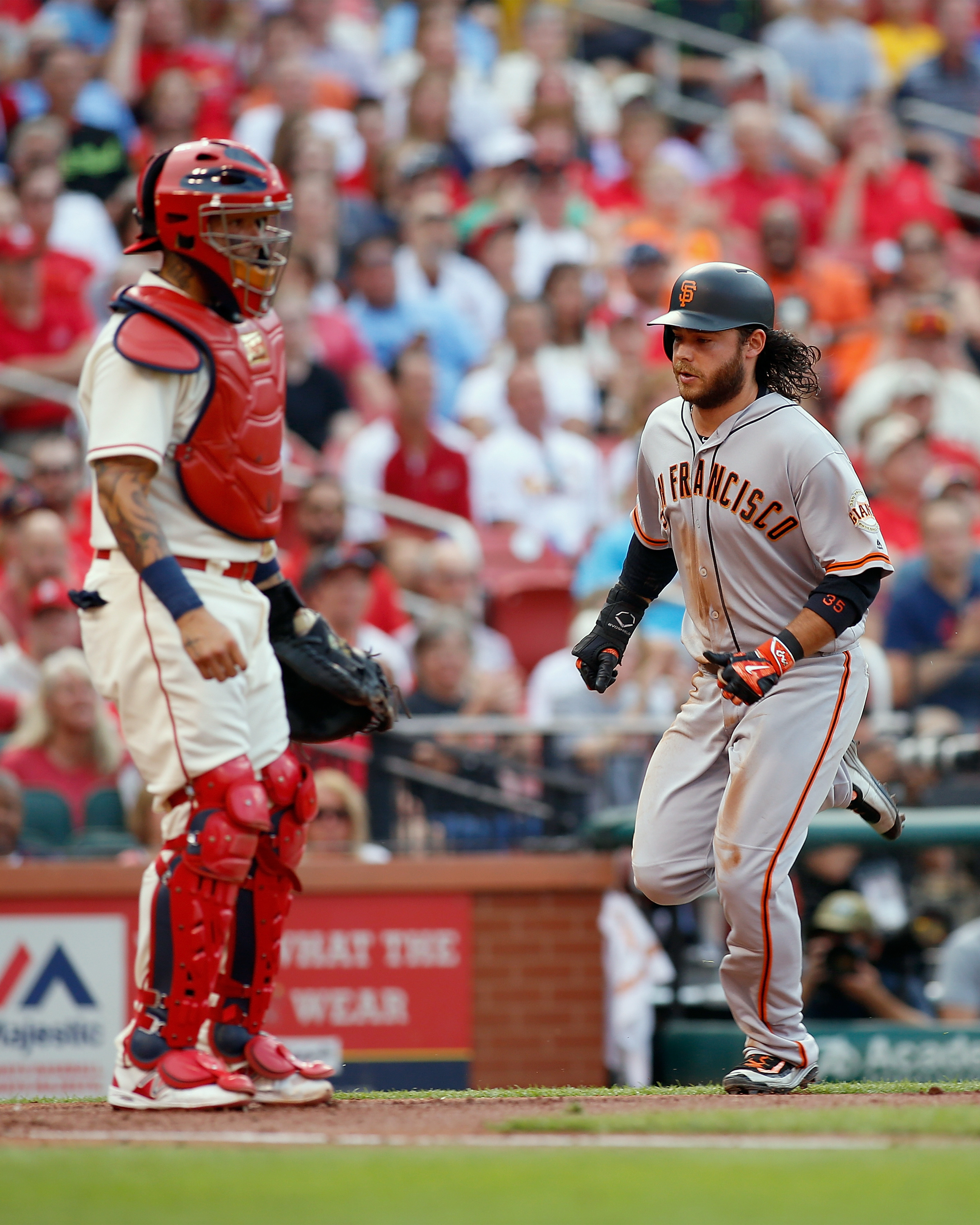 St. Louis Cardinals catcher Yadier Molina, left, looks on as San Francisco Giants' Brandon Crawford scores a run during the second inning of a baseball game Saturday, June 4, 2016, in St. Louis. (AP Photo/Scott Kane)