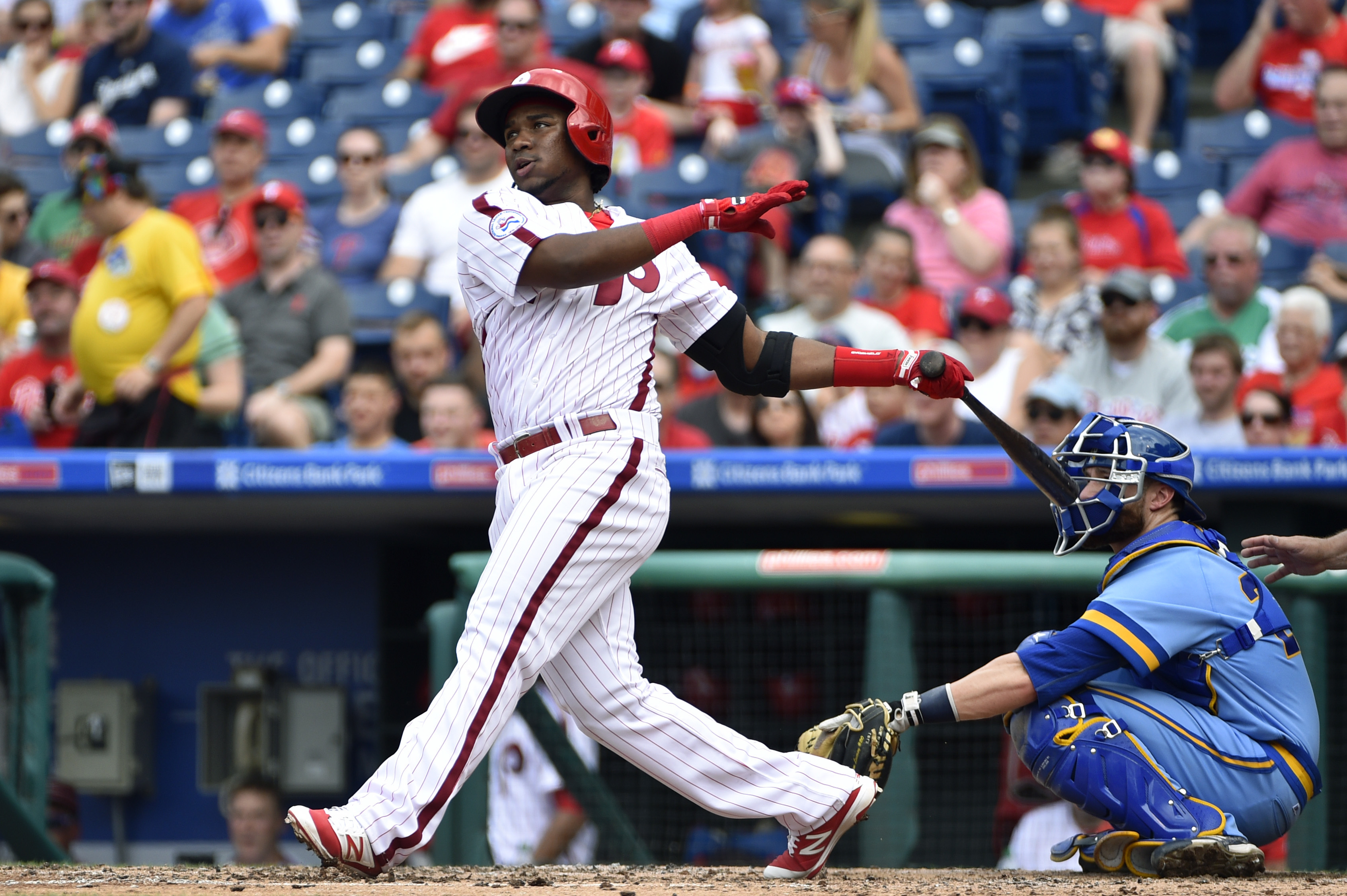 Philadelphia Phillies' Maikel Franco, center, hits a home run off Milwaukee Brewers starting pitcher Wily Peralta during the third inning of a baseball game, Sunday, June 5, 2016, in Philadelphia. (AP Photo/Derik Hamilton)