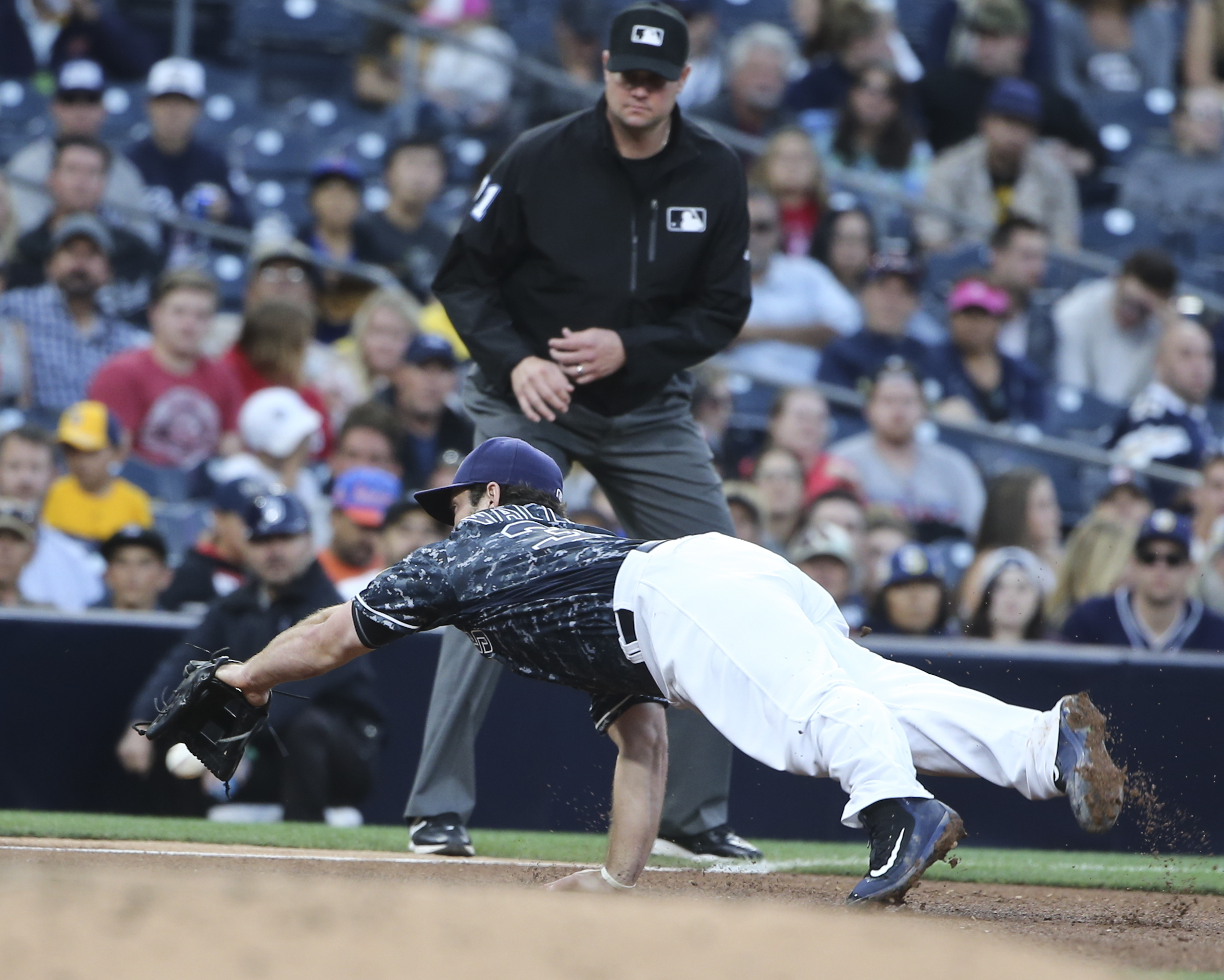 San Diego Padres third baseman Brett Wallace misses on his diving attempt on a ball that went for for a double by Colorado Rockies' Trevor Story in the fifth inning of a baseball game Sunday June 5, 2016 in San Diego. The double drove in a run. (AP Photo/